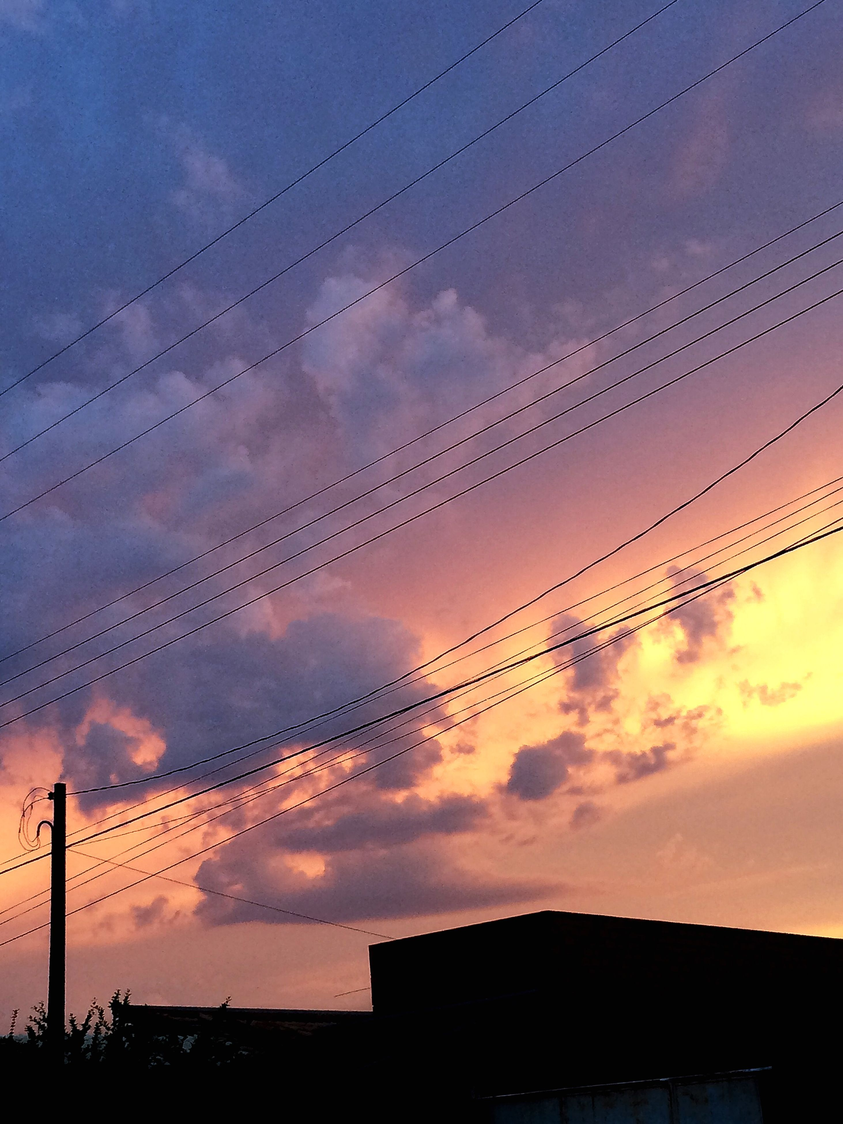 low angle view, silhouette, sunset, sky, power line, built structure, architecture, cable, bird, cloud - sky, connection, building exterior, electricity pylon, electricity, dusk, animal themes, cloud, power supply, outdoors, orange color