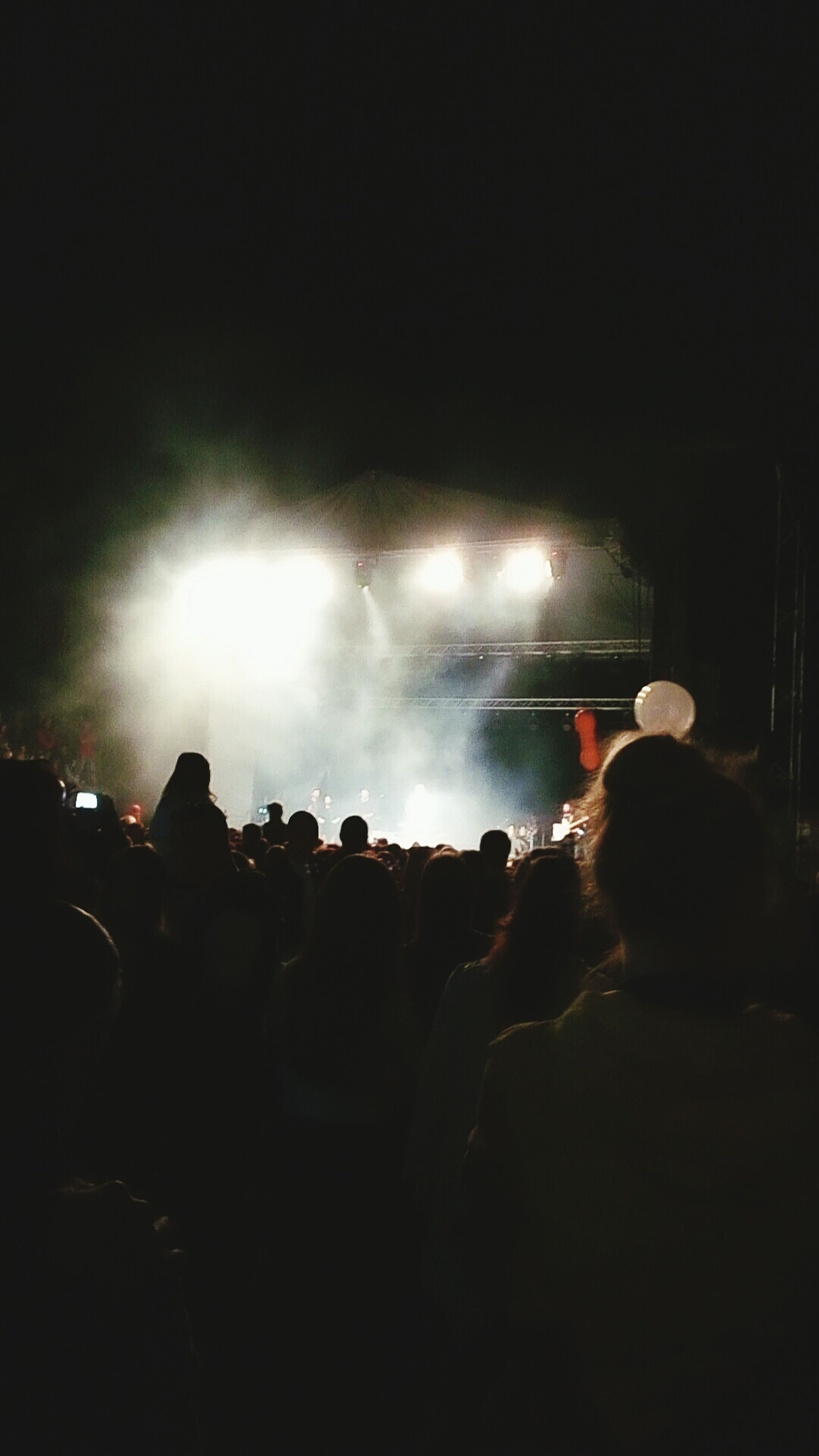 arts culture and entertainment, large group of people, illuminated, night, rear view, crowd, event, men, person, nightlife, enjoyment, performance, stage - performance space, popular music concert, dark, fun, atmosphere, concert, spectator, music festival, atmospheric mood, sky
