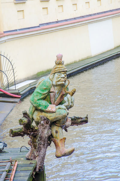 Gnome statue sitting by river Figure Riverside Sitting Architecture Art And Craft Gnome River Sculpture Statue