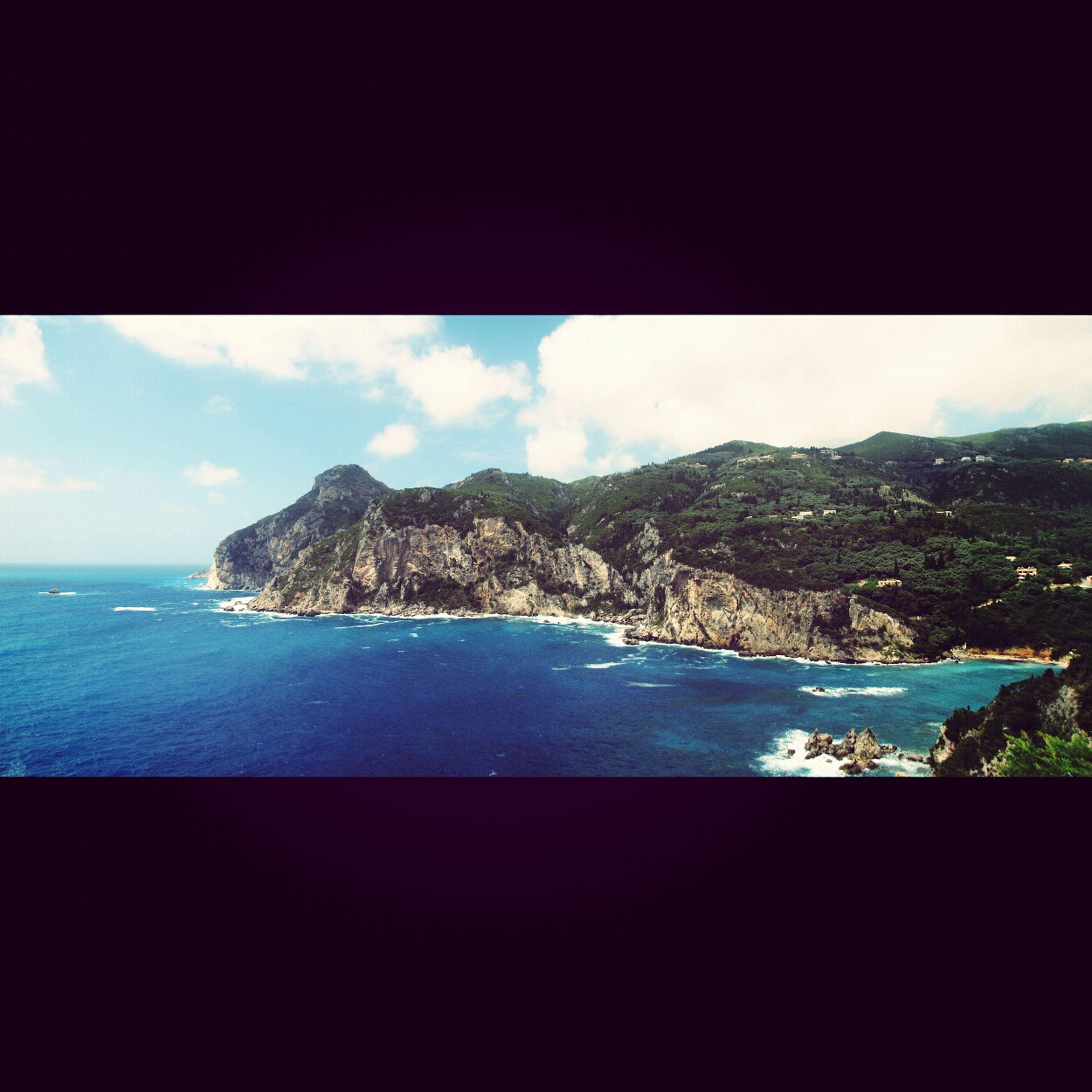 sea, water, sky, scenics, mountain, beauty in nature, tranquil scene, tranquility, horizon over water, nature, cloud - sky, idyllic, beach, coastline, blue, mountain range, shore, cloud, rock - object, day