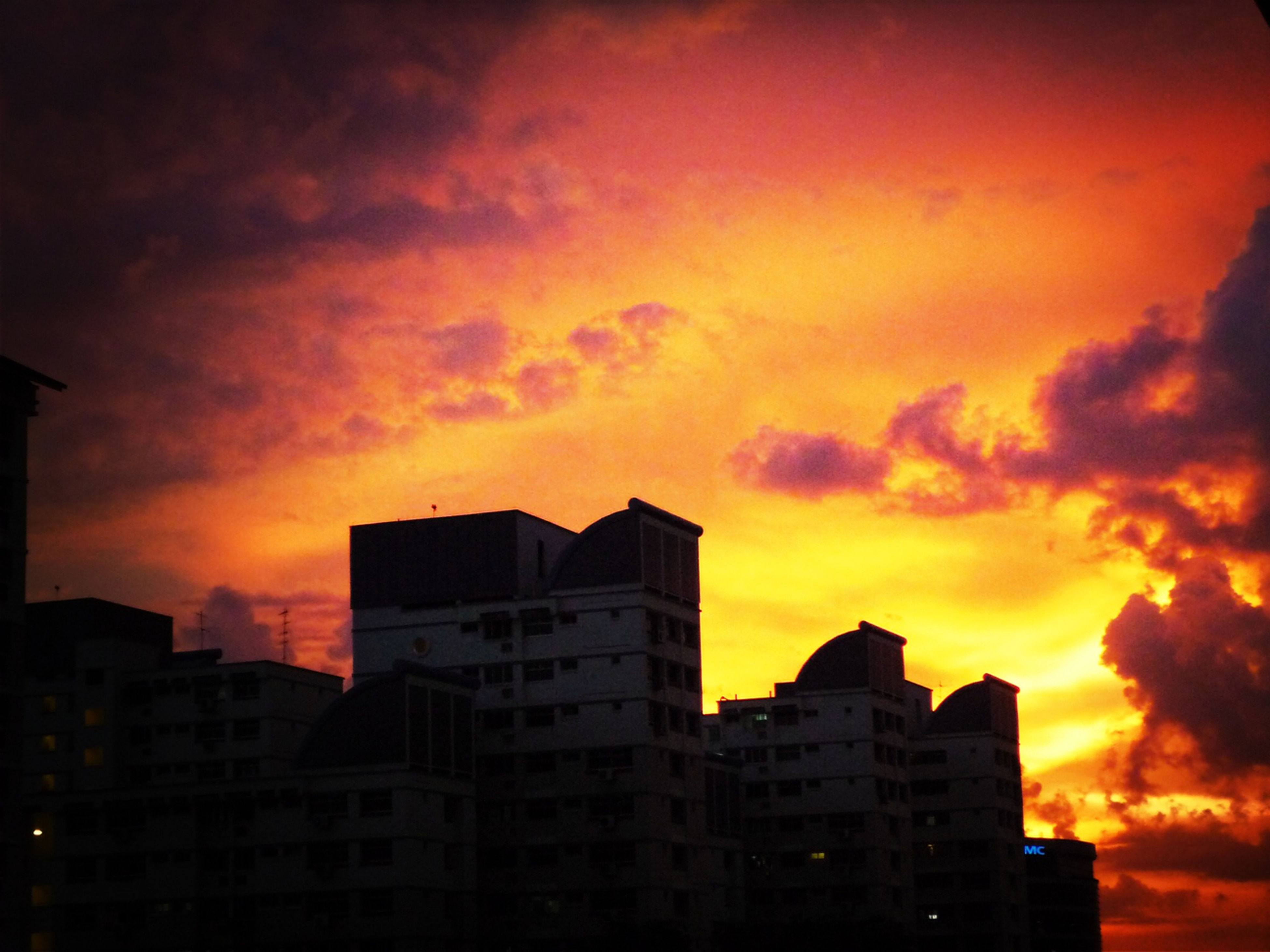 sunset, orange color, building exterior, architecture, sky, built structure, cloud - sky, silhouette, dramatic sky, low angle view, cloudy, city, beauty in nature, cloud, building, scenics, nature, moody sky, overcast, weather