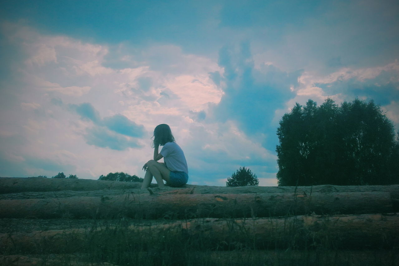 sitting, sky, cloud - sky, one person, real people, outdoors, women, full length, nature, tree, day, young women, beauty in nature, young adult, people