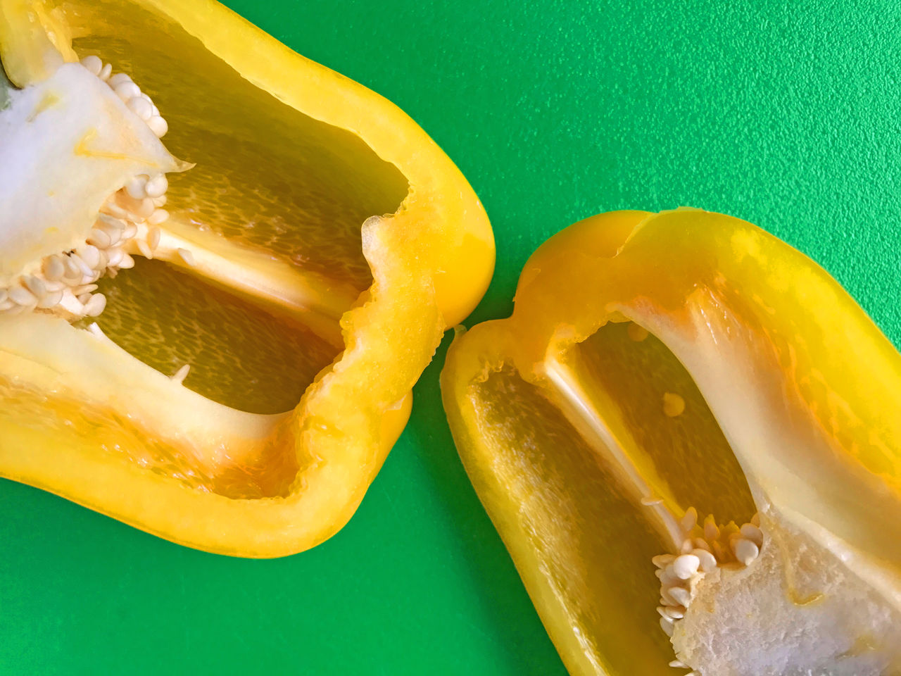 Yellow bell pepper on green Bell Pepper Close-up Contrast Copy Space Food Ingredient Food Preparation Fresh Green Color Healthy Eating Indoors  Natural Light No People Overhead Phone Camera Produce Saturated Colors Seeds Textures Vegan Yellow