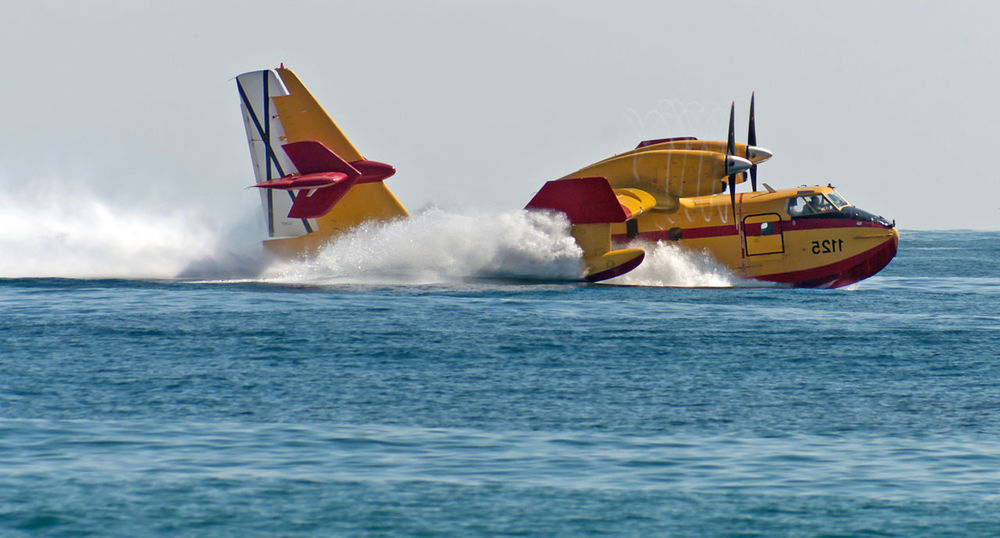 Fire fighting plane collecting water Bombardier Plane Seaplane Day Fire Fighting Hydroplane Mode Of Transport Outdoors Sea Sky Transportation Water Water Bomber