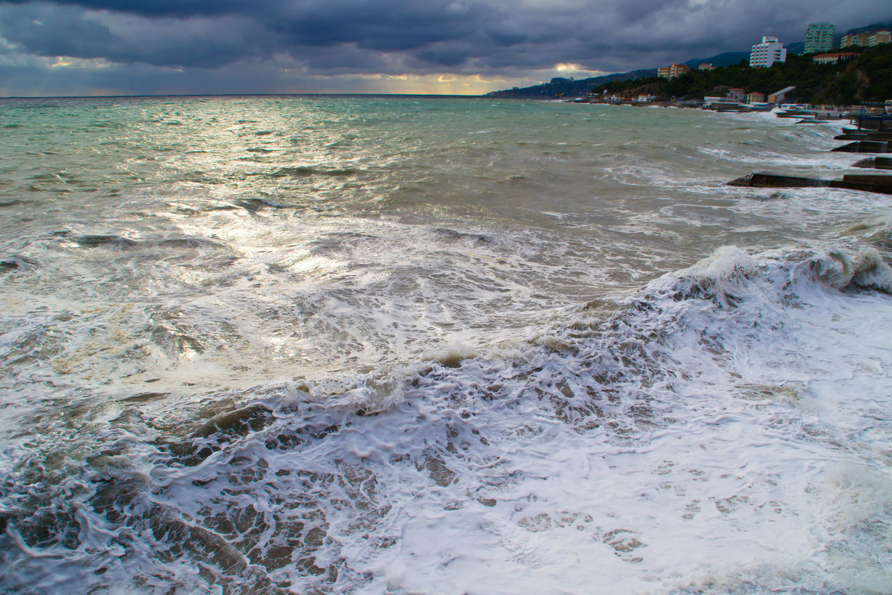 Waves Splashing On Rocks In Sea By City Against Cloudy Sky
