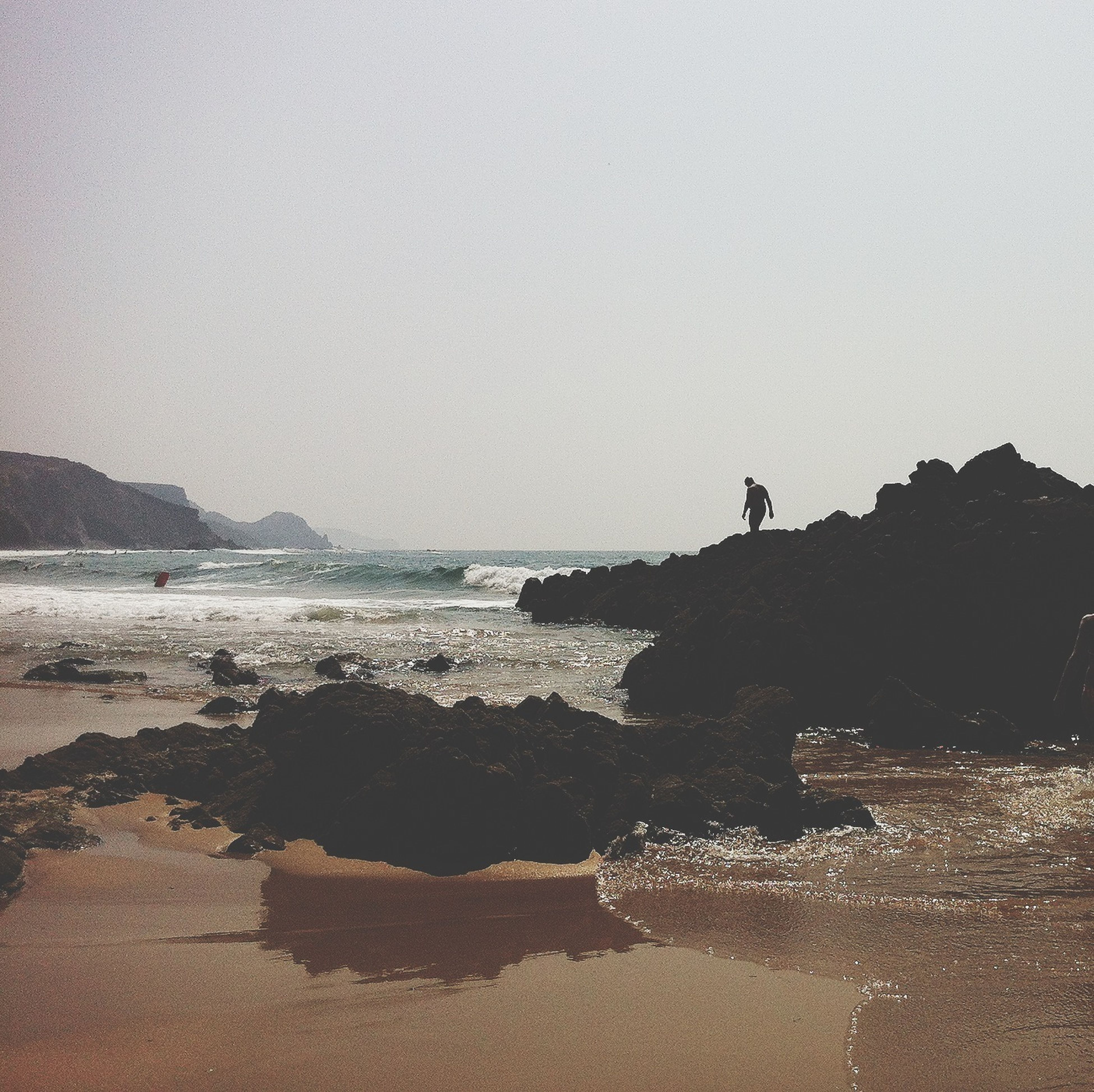 water, sea, clear sky, beach, copy space, shore, scenics, tranquil scene, silhouette, nature, beauty in nature, tranquility, horizon over water, sand, wave, rock - object, sky, outdoors, coastline
