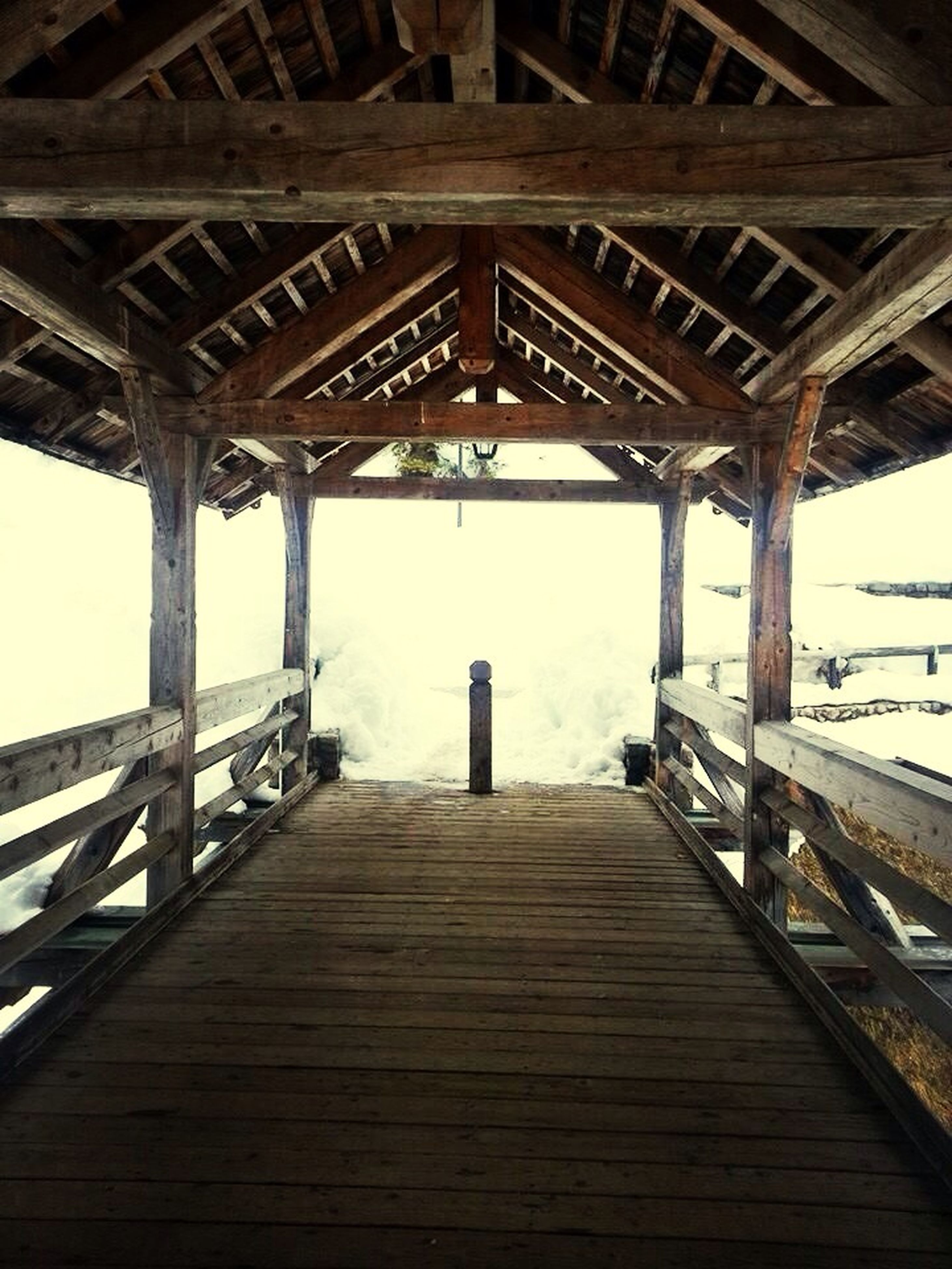 built structure, architecture, wood - material, the way forward, low angle view, diminishing perspective, bridge - man made structure, connection, railing, architectural column, sky, bridge, wooden, day, indoors, engineering, sunlight, vanishing point, pier, long