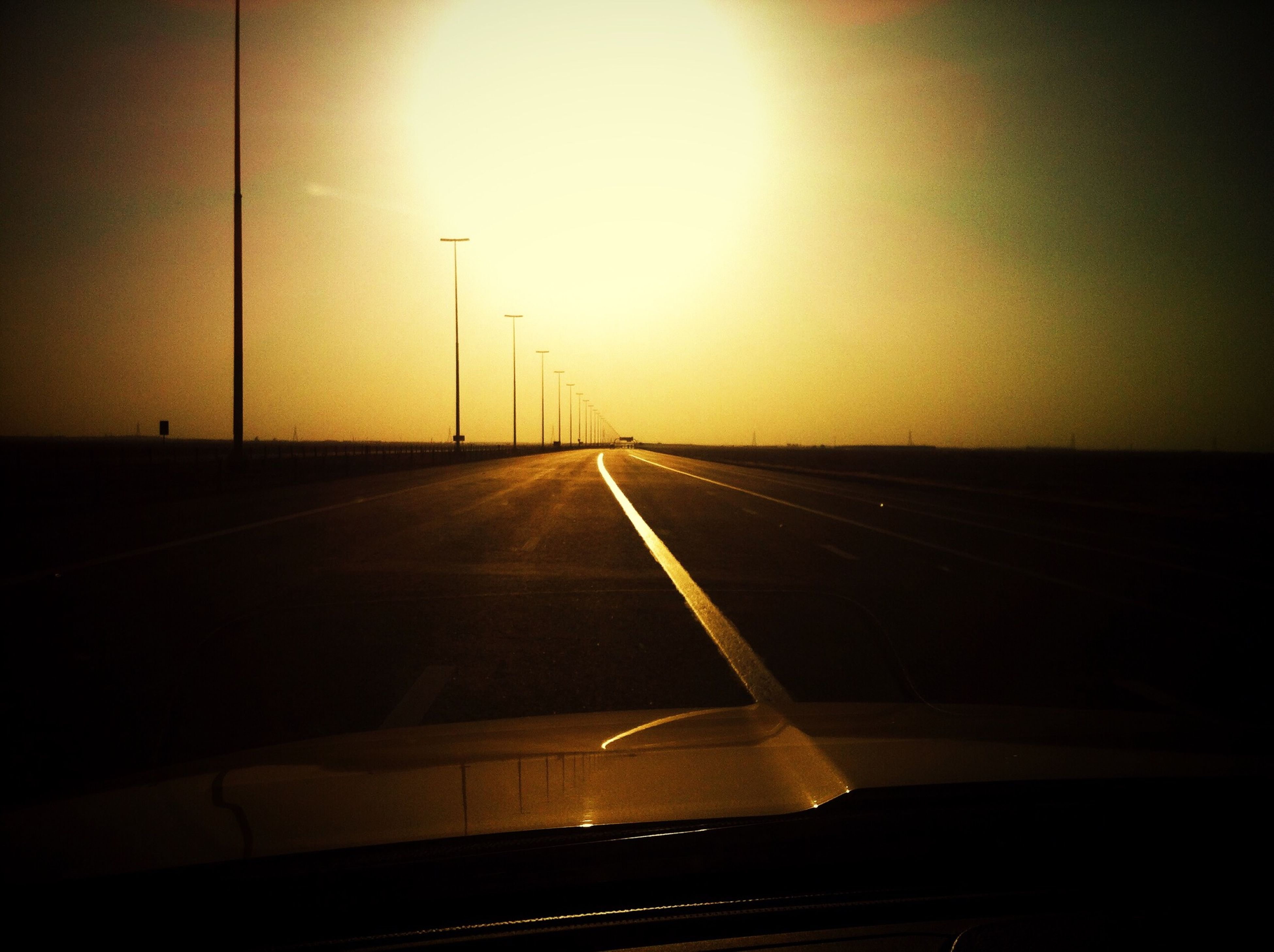 transportation, the way forward, diminishing perspective, vanishing point, road, road marking, sunset, sky, mode of transport, empty, long, car, street light, no people, travel, empty road, highway, outdoors, on the move, landscape