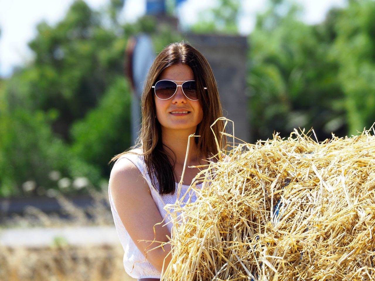 Young Woman In Sunglasses Standing By Dry Grass