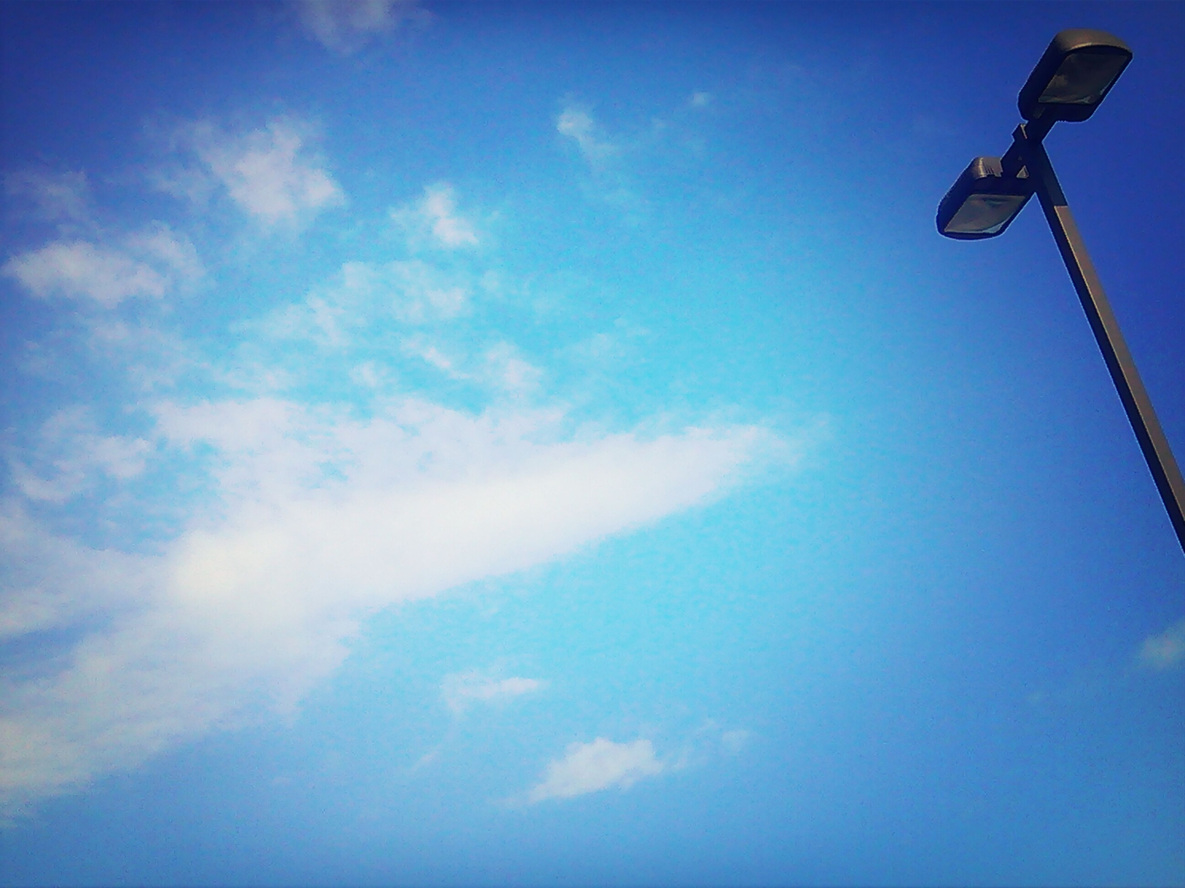 low angle view, blue, sky, cloud - sky, street light, lighting equipment, tranquility, nature, beauty in nature, vapor trail, cloud, outdoors, scenics, electricity, no people, day, tranquil scene, technology, pole, copy space