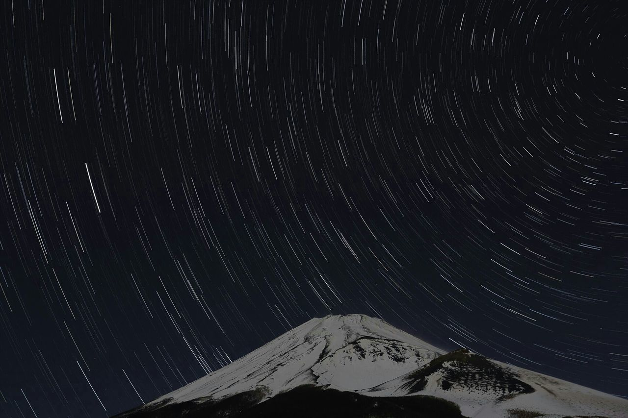 Idyllic View Of Star Trails Over Snowcapped Mountain