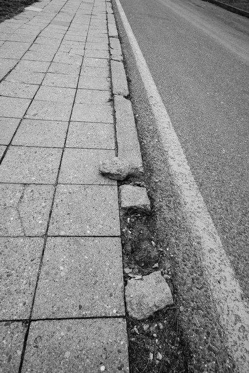 Demolished curbside of a sidewalk Road Asphalt Black And White Black And White Photography Broken City Curbside Day Demolished Destroyed Kerbside Nature No People Outdoors Road Side View Street Transportation Vertical Format