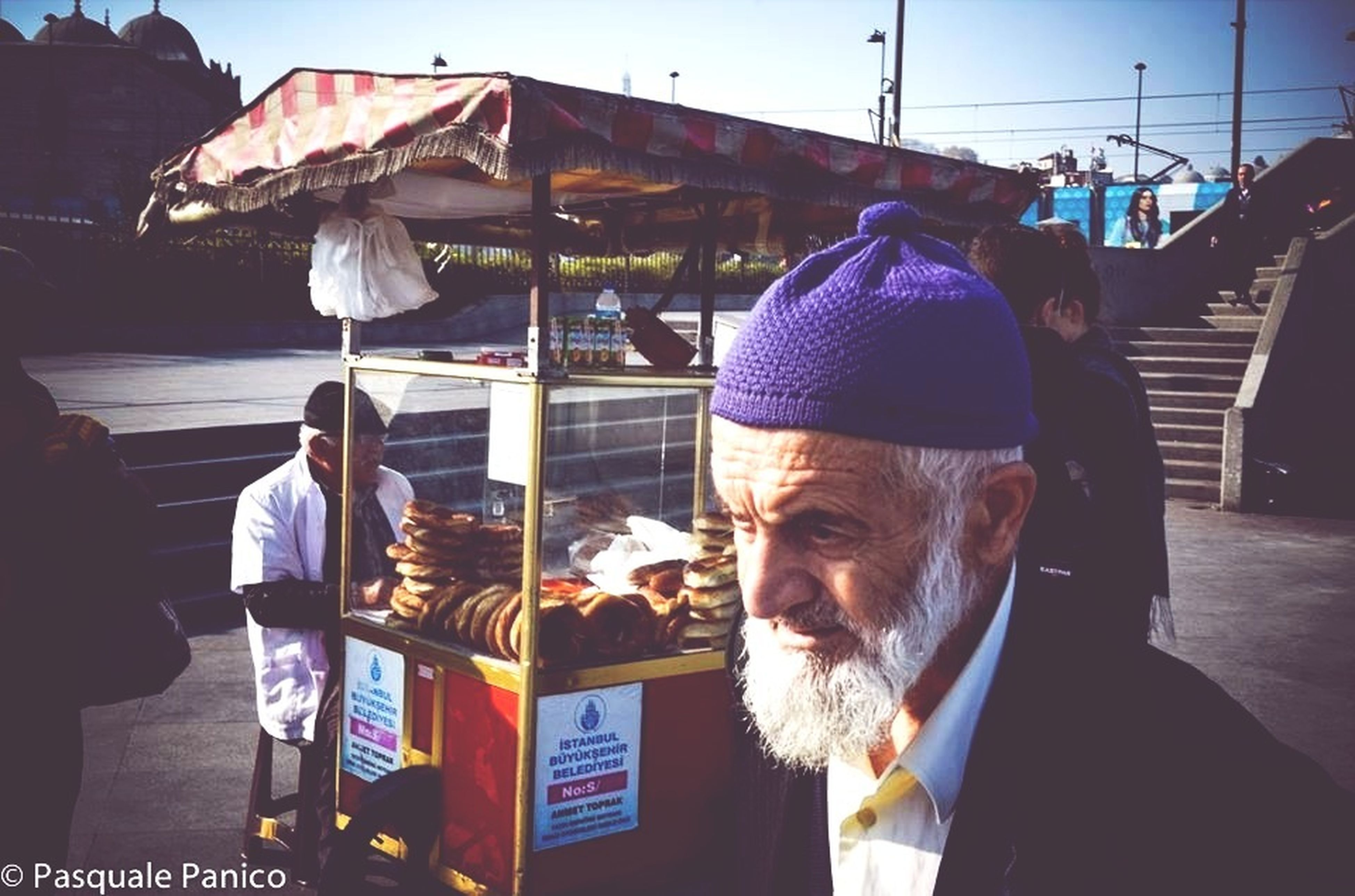 men, lifestyles, person, food and drink, leisure activity, street, transportation, rear view, casual clothing, incidental people, food, day, sitting, market, city, medium group of people, sunlight, outdoors