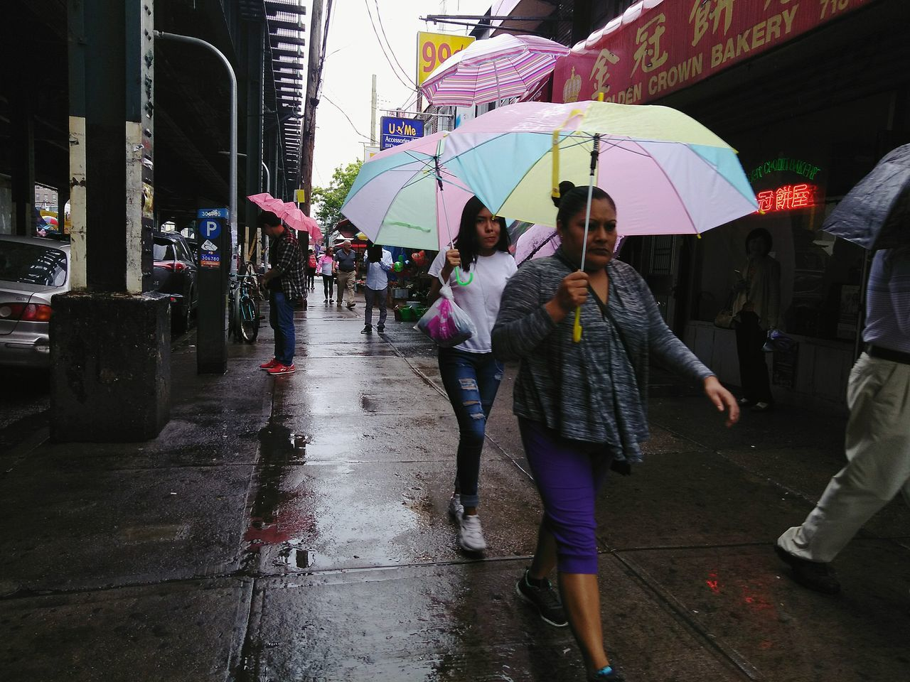 umbrella, rain, rainy season, real people, wet, protection, walking, weather, lifestyles, shelter, outdoors, leisure activity, women, under, day, below, enjoyment, full length, men, togetherness, large group of people, architecture, city, adult, people