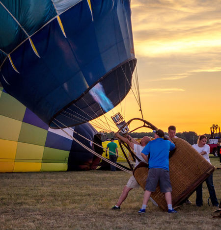 July 3 2017; a team works during a colorful sunset, to fill their hot air balloon during an air show in Michigan USA Event Hot Air Balloons Tea Adult Air Show Basket Day Editorial  Editorial Photography Friendship Full Length Hot Air Balloon Inflating Leisure Activity Lifestyles Men Nature Outdoors Real People Sky Sport Standing Sunset Team Work Transportation