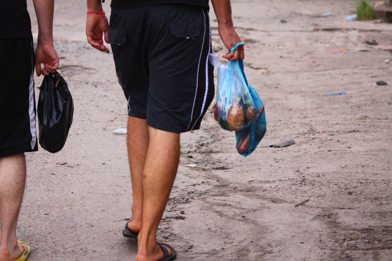 EyeEm Selects Low Section Human Body Part A Day In The Market Market Day Going Home From The Market Buying Food From The Market Lifestyle Living In Asia Two People Togetherness Friendship Walking Outdoors Purist In Photography Sihanoukville Cambodia Only Men Walking Back Home Plastic Bags Carrying