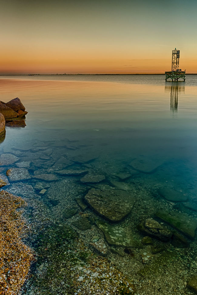 The fill rocks used to build the Texas City dike are visible in the shallow waters of Galveston Bay Beauty In Nature Calm Horizon Over Water Idyllic Nature No People Non-urban Scene Ocean Orange Color Outdoors Remote Rippled Scenics Sea Sky Sunset Tranquil Scene Tranquility Water