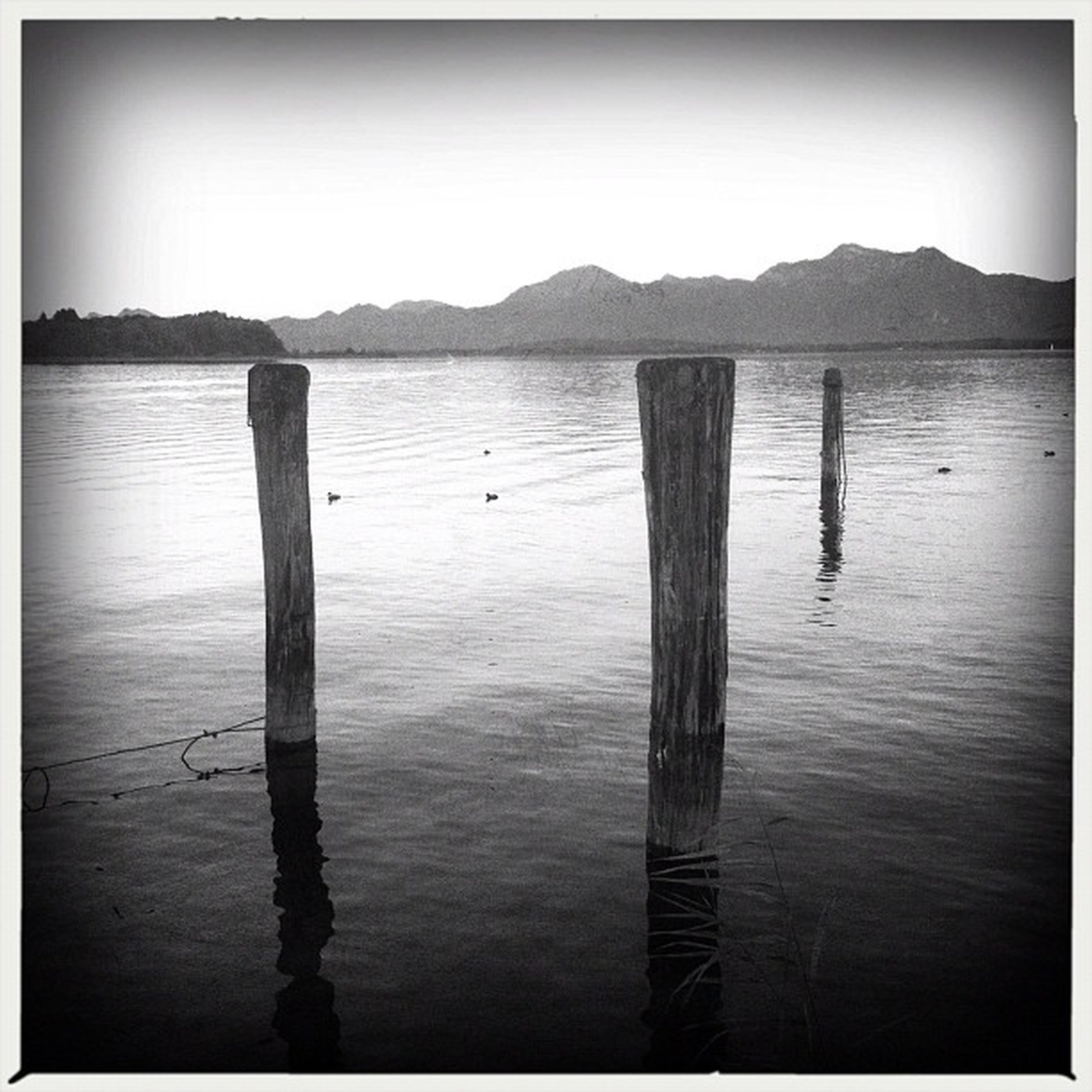 transfer print, water, auto post production filter, tranquility, tranquil scene, wooden post, wood - material, sea, scenics, lake, beauty in nature, nature, mountain, clear sky, pier, sky, pole, reflection, idyllic, rippled