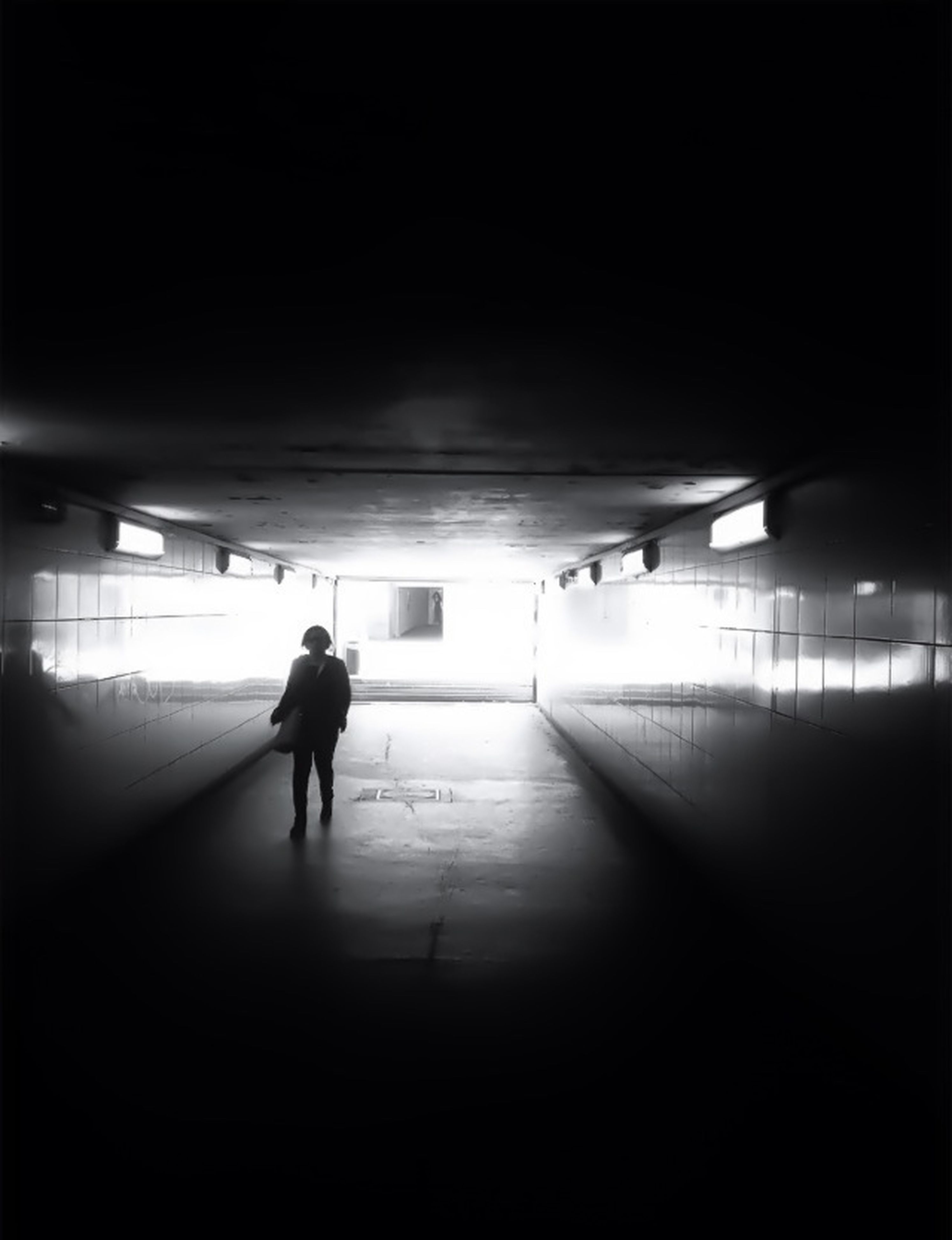walking, men, full length, indoors, lifestyles, rear view, architecture, built structure, silhouette, person, illuminated, leisure activity, tunnel, the way forward, subway, standing, on the move