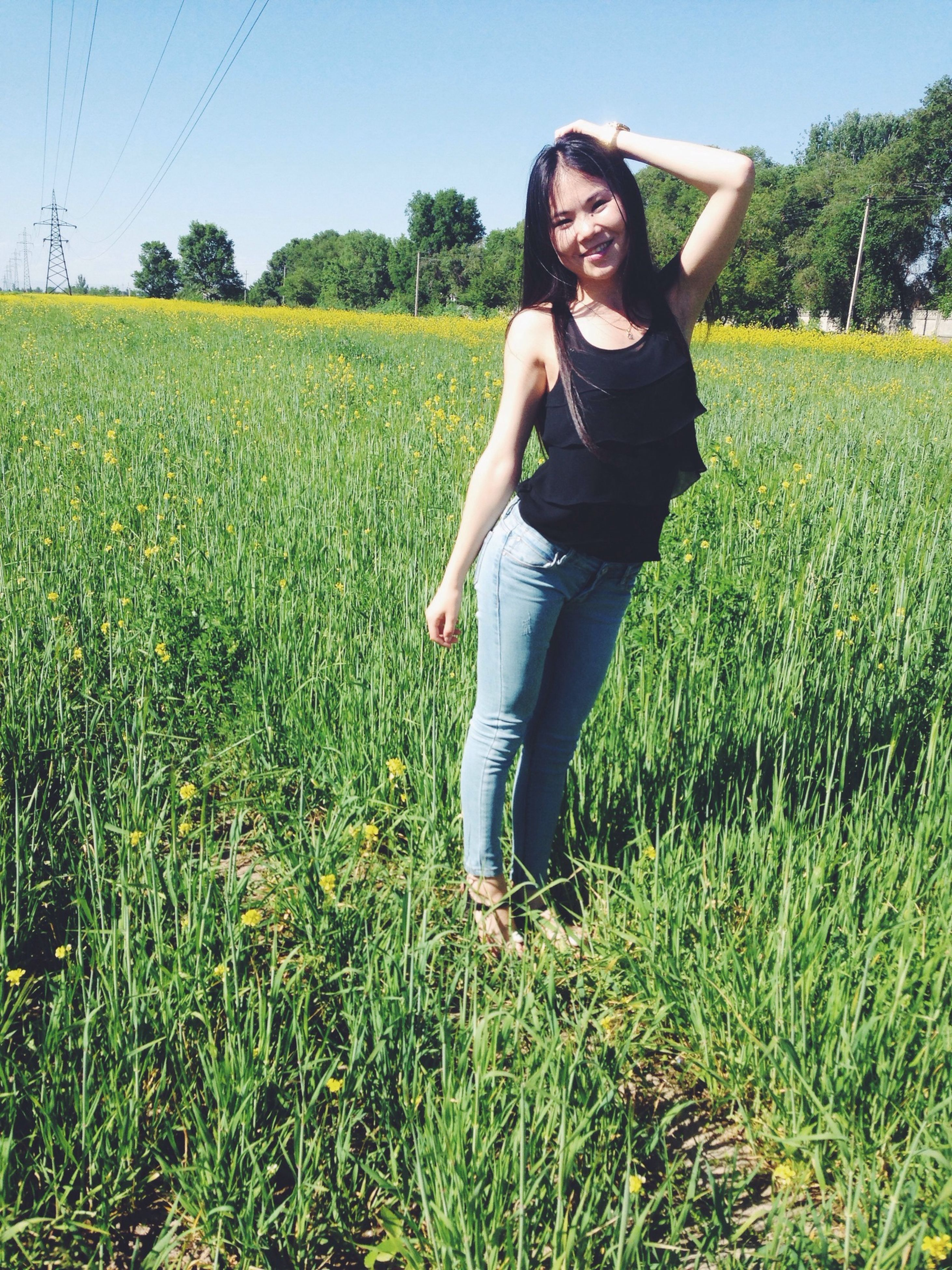 grass, young adult, person, lifestyles, field, casual clothing, leisure activity, young women, full length, standing, growth, green color, grassy, plant, tree, clear sky, nature, front view