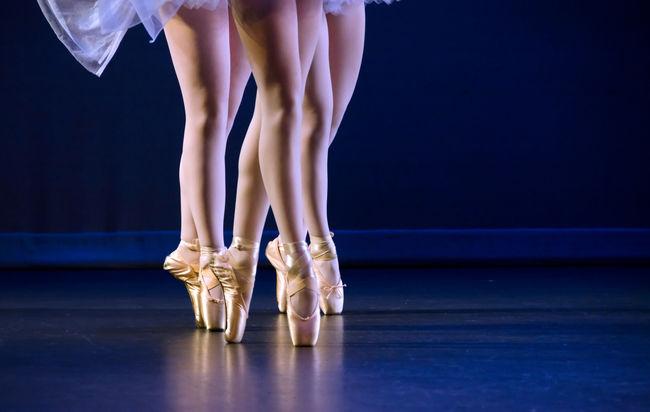 Feet of trio of ballerinas on pointe dark blue floor Ankle Balerina Ballet Performance Dancer Femininity Foot Footwear Leisure Activity Recital