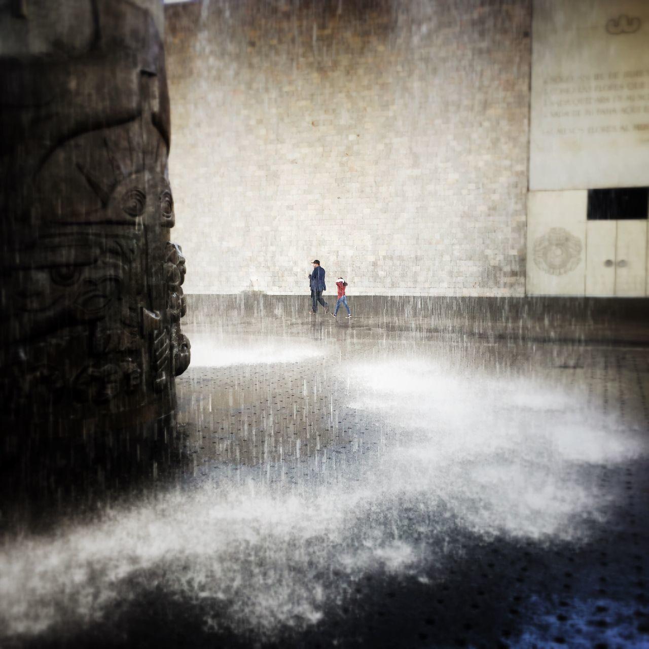 People Walking Against Wall Seen Through Fountain