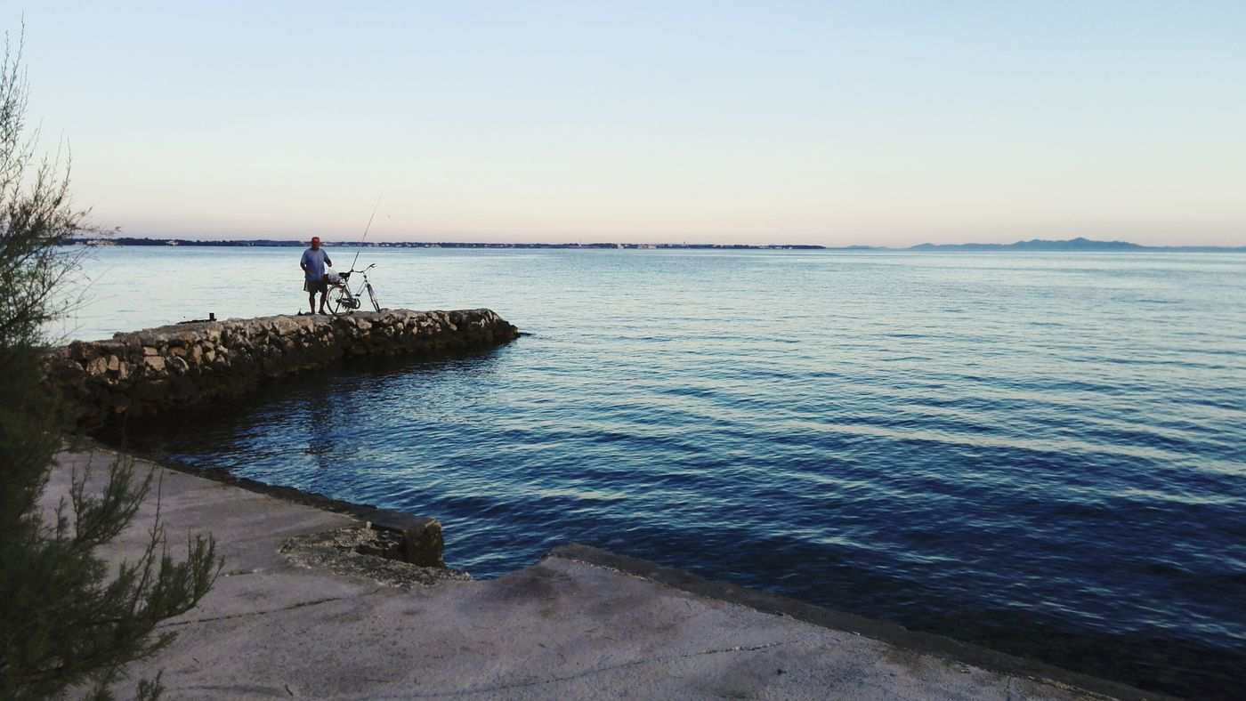 Water Scenics Clear Sky Tranquil Scene Tranquility Sea Calm Beauty In Nature Nature Blue Outdoors Non-urban Scene Solitude Ocean Coastline Distant Vacations Fishing