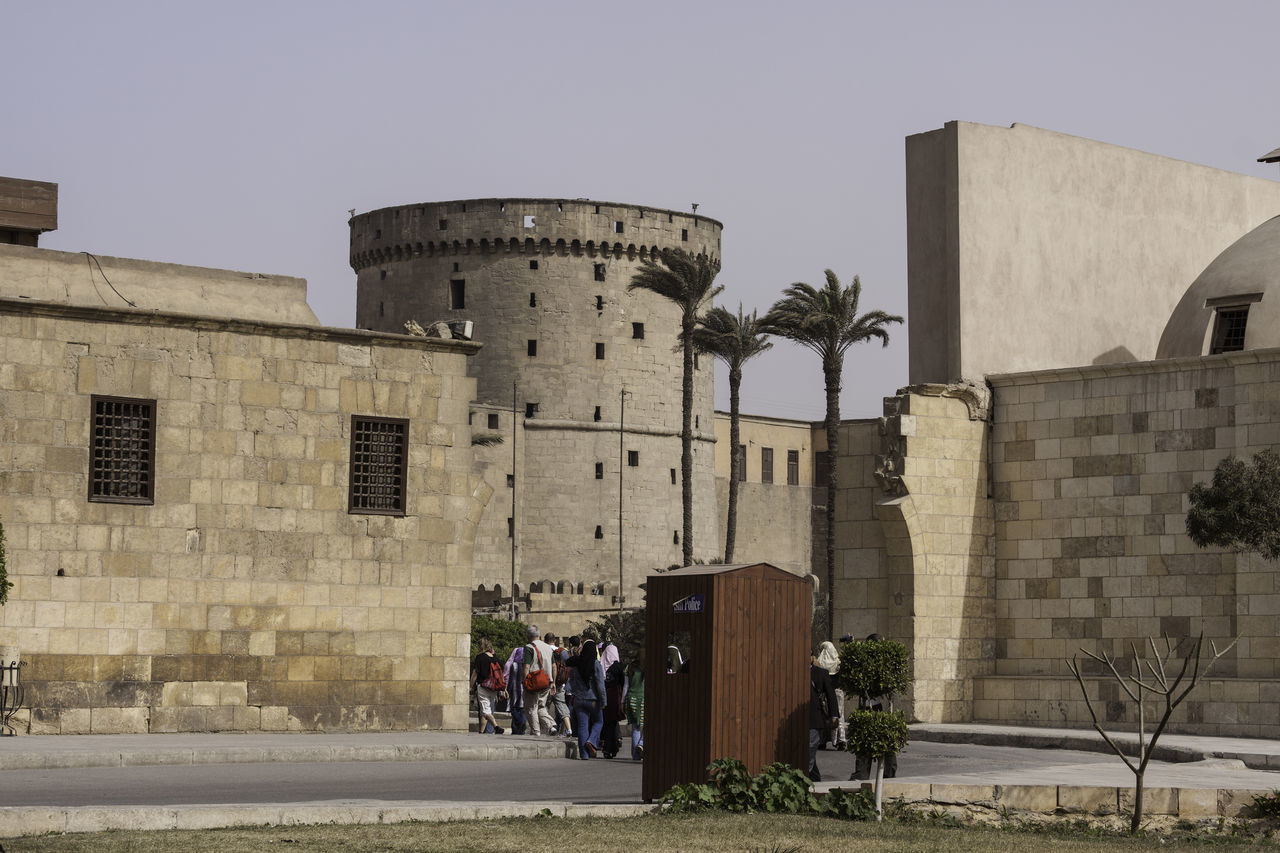 Visitors walking in through the entry gates of the Saladin Citadel in Cairo, Egypt. The heritage buildings are all right ahead. The Saladin Citadel is built on the Mokattam hill near the center of Cairo, and is a famous tourist attraction. It is a well preserved site, with mosques and other buildings. Saladin is the most famous historic Arabic ruler, and he fortified this citadel in the 12th century to protect it against attack. The Citadel was build to be the heart of a defensive fortification, and was the center of Egyptian power till the 19th century, when the power was moved to the Abdin Palace in the 1860's. The Citadel contains 3 mosques, and some museums. The Citadel provides a great view of the city of Cairo. The original aim of Saladin was to build a wall that would encompass both Cairo and Fustat. The wall took a number of years to build. As an effort to provide water to the Citadel, Saladin had also built a deep well, the Well of Joseph (can still be seen today), and from there, the water was moved all over the Citadel. Then, another ruler, al-Nasir Muhammed improved the water system and also constructed the mosque, the Mosque of Nasir in the year 1318. Another mosque was built between the years 1828 and 1848, called the Mosque of Muhammed Ali, and is located at the highest point of the Citadel. This mosque replaced the earlier Mosque of Nasir as the state mosque. In addition, there are 2 other mosques located in the Citadel. Architecture Building Exterior Built Structure Cairo Cairo Egypt Clear Sky Day Egypt Egypt Cairo History Medieval Medieval Architecture Outdoors People Real People Saladin Citadel Saladin Citadel Of Cairo Sky Travel Destinations