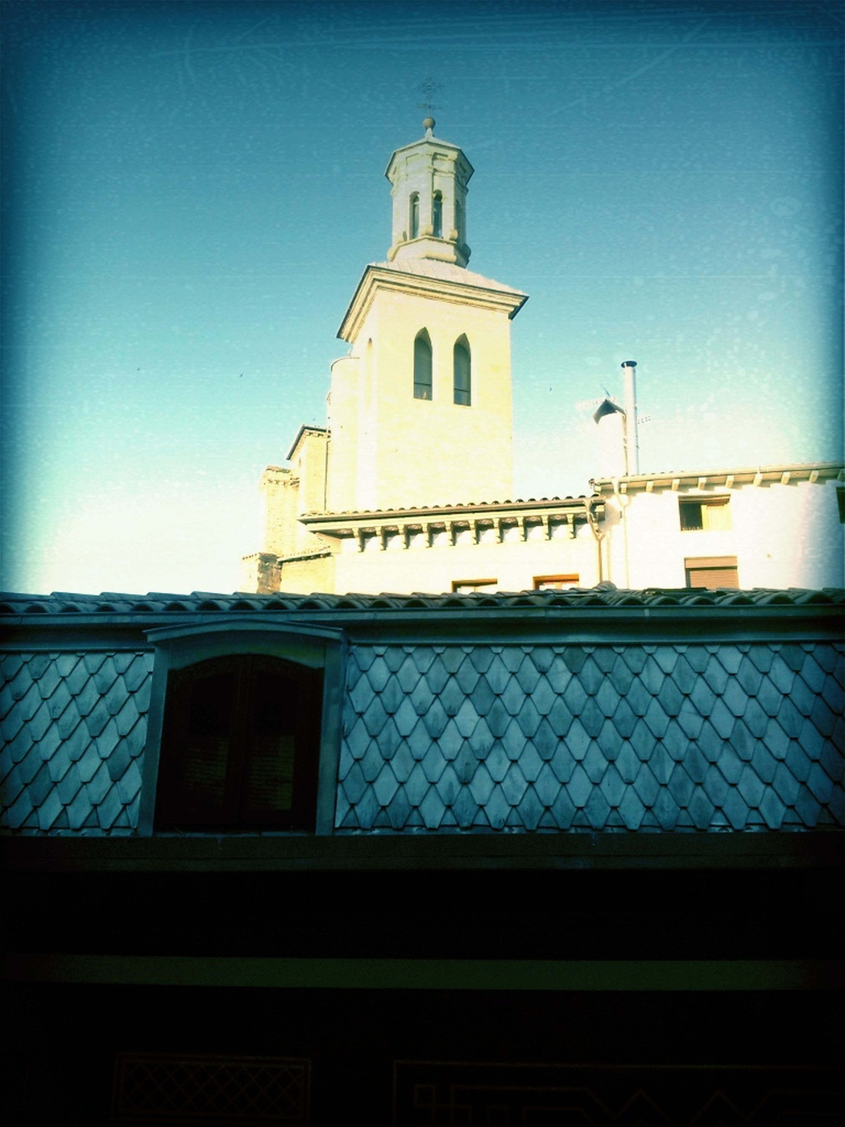 architecture, building exterior, built structure, church, religion, place of worship, clear sky, low angle view, spirituality, blue, window, cross, sunlight, house, tower, sky, copy space, day
