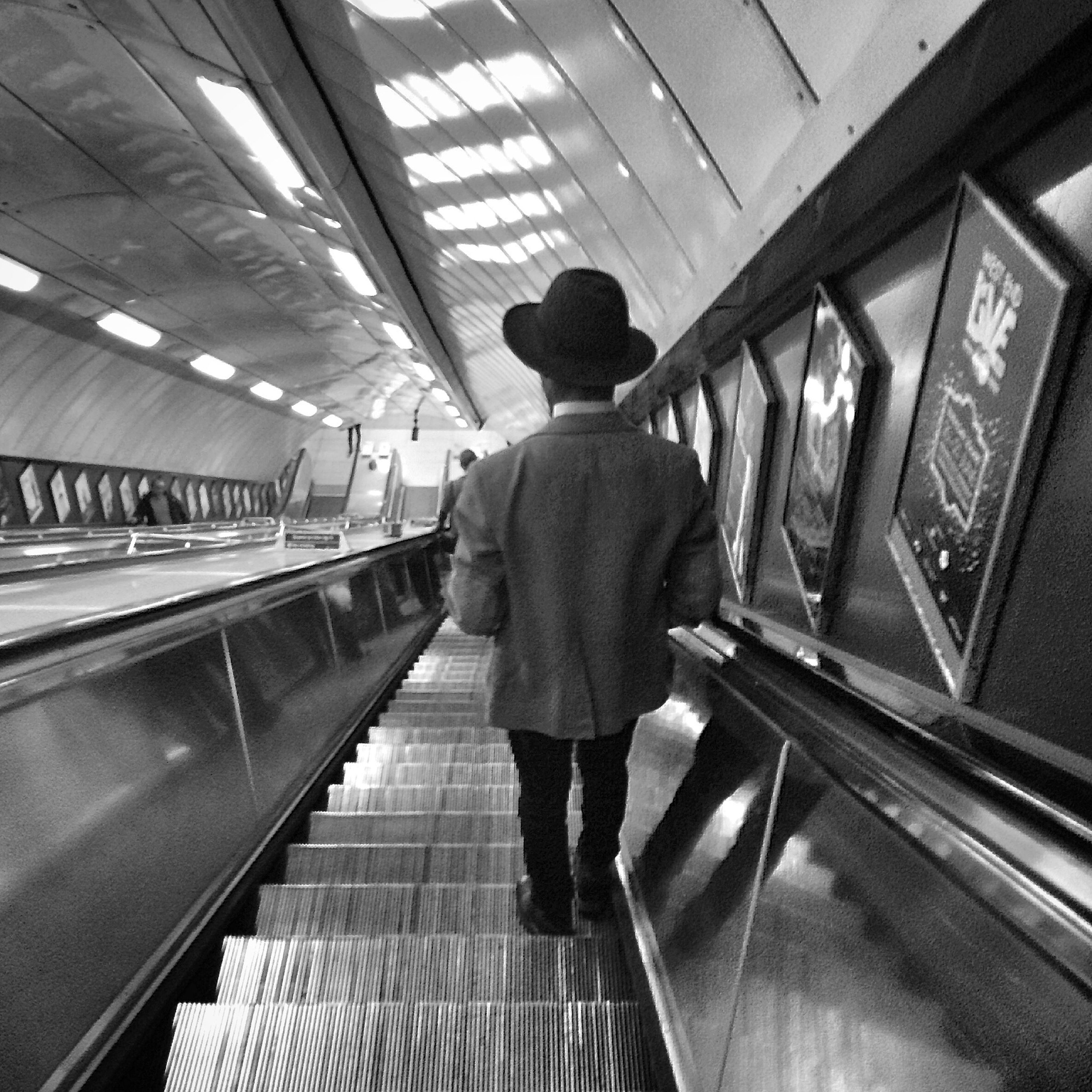 indoors, lifestyles, rear view, full length, escalator, ceiling, railing, men, steps, leisure activity, walking, standing, steps and staircases, railroad station, architecture, casual clothing, built structure, person