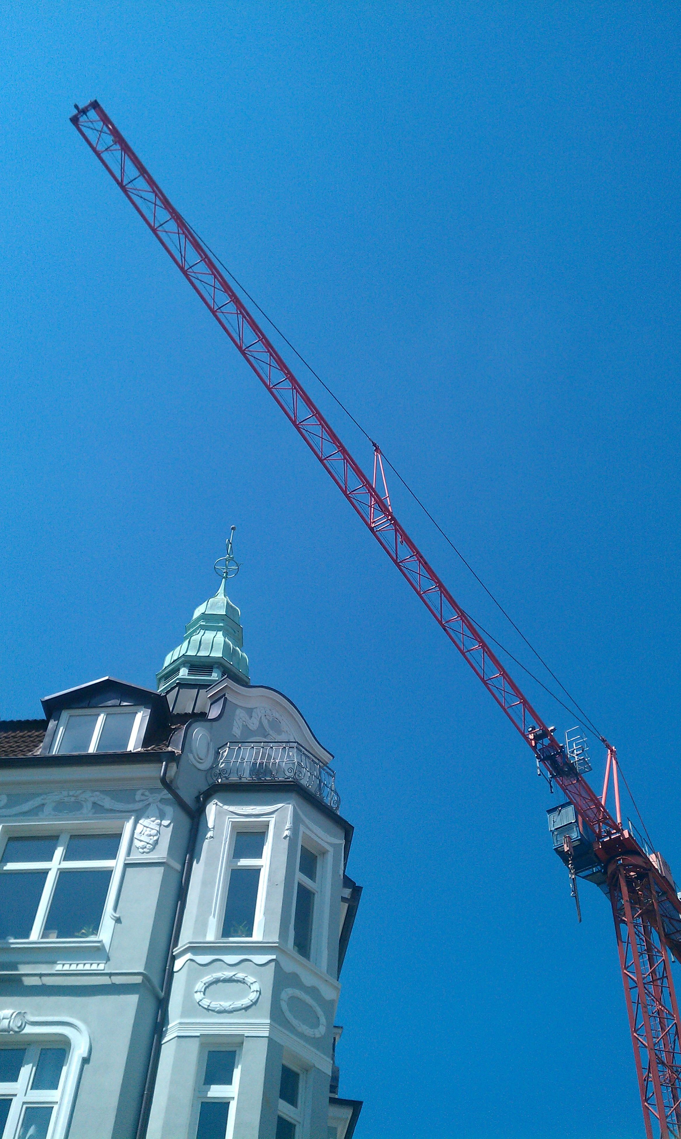 low angle view, architecture, built structure, building exterior, clear sky, crane - construction machinery, blue, construction site, copy space, development, crane, construction, tall - high, high section, tower, outdoors, day, city, no people, building