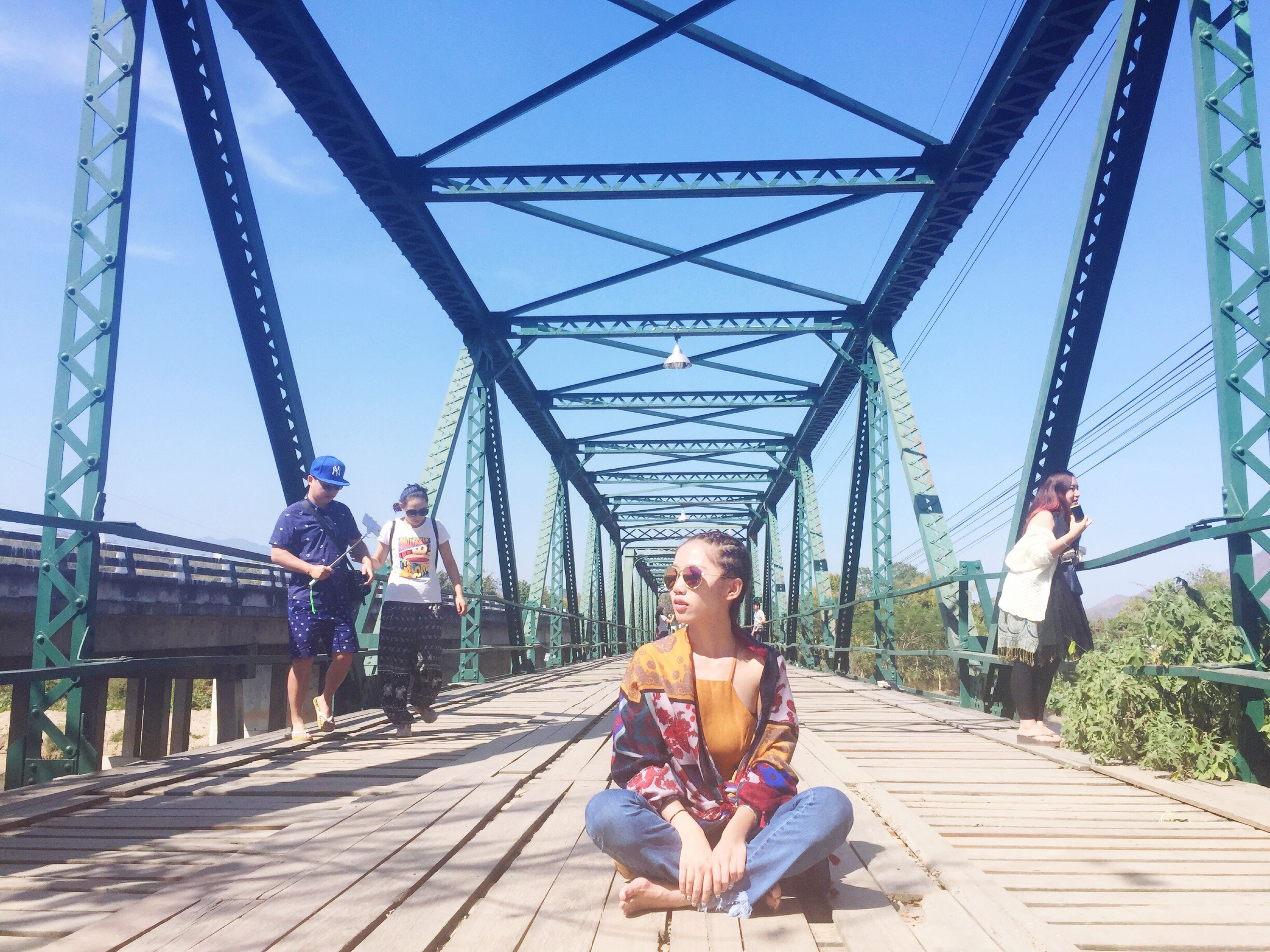 lifestyles, leisure activity, casual clothing, built structure, architecture, person, full length, bridge - man made structure, railing, young adult, travel, young women, sunlight, connection, childhood, day, looking at camera, tourism
