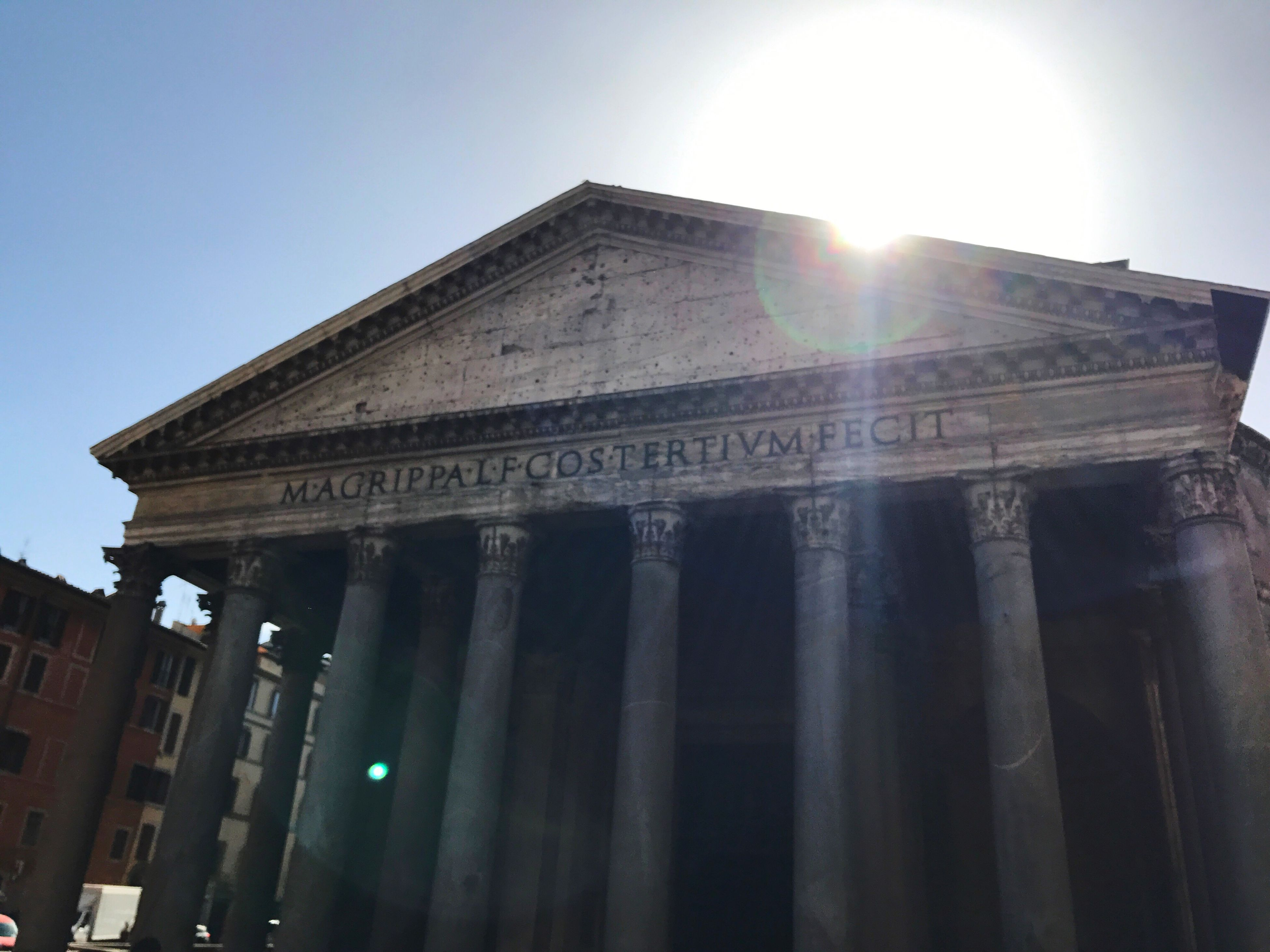 architecture, built structure, sunlight, low angle view, building exterior, sunbeam, text, lens flare, tourism, travel, travel destinations, history, clear sky, architectural column, outdoors, city, sky, no people, day, pediment, city gate