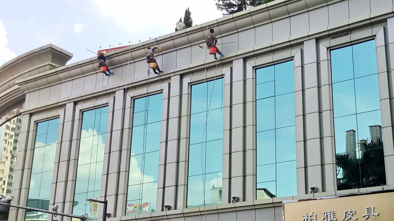 Window Washers Hanging From Modern Building In City