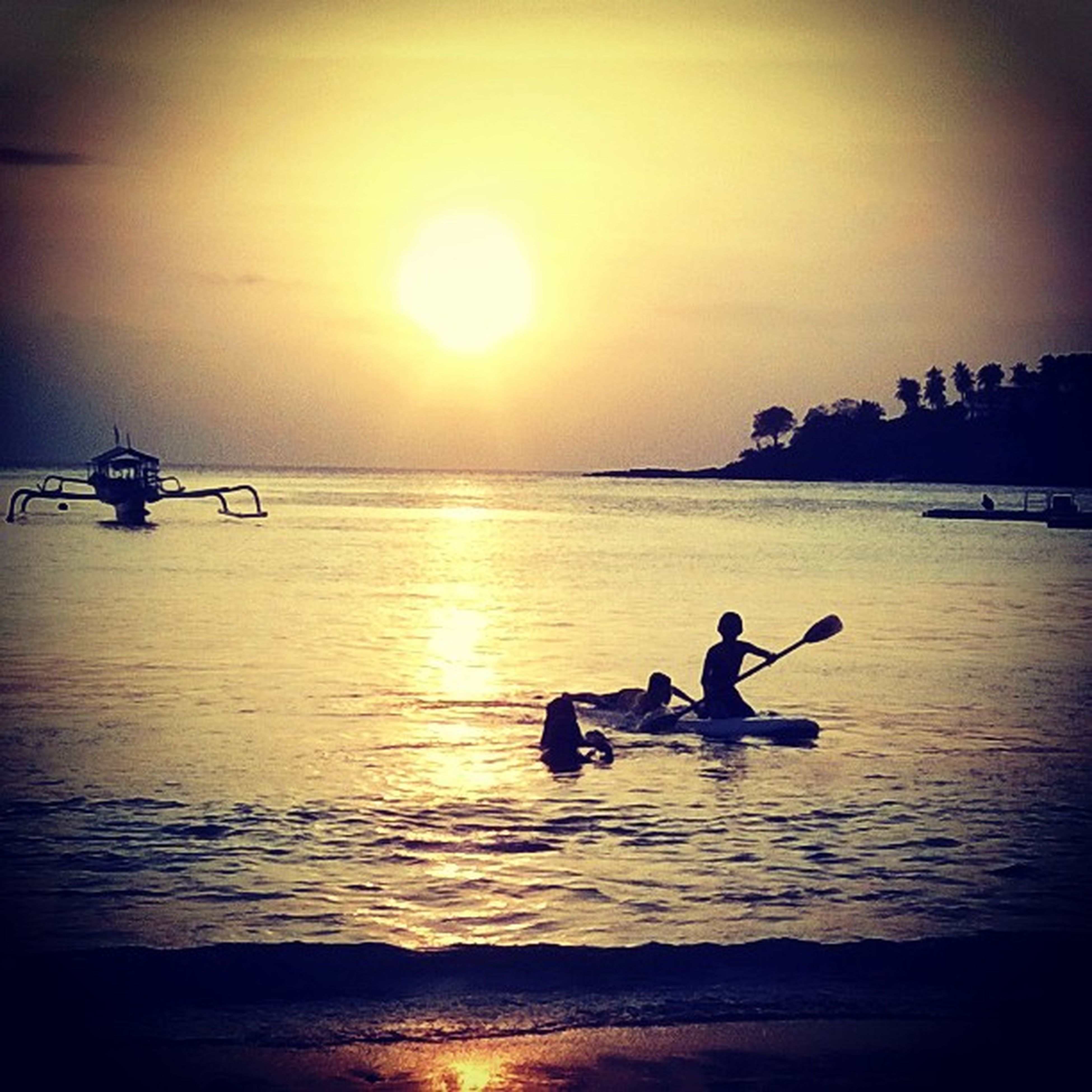 water, sunset, sea, silhouette, leisure activity, lifestyles, men, beach, horizon over water, sun, sky, reflection, scenics, transportation, beauty in nature, tranquility, tranquil scene
