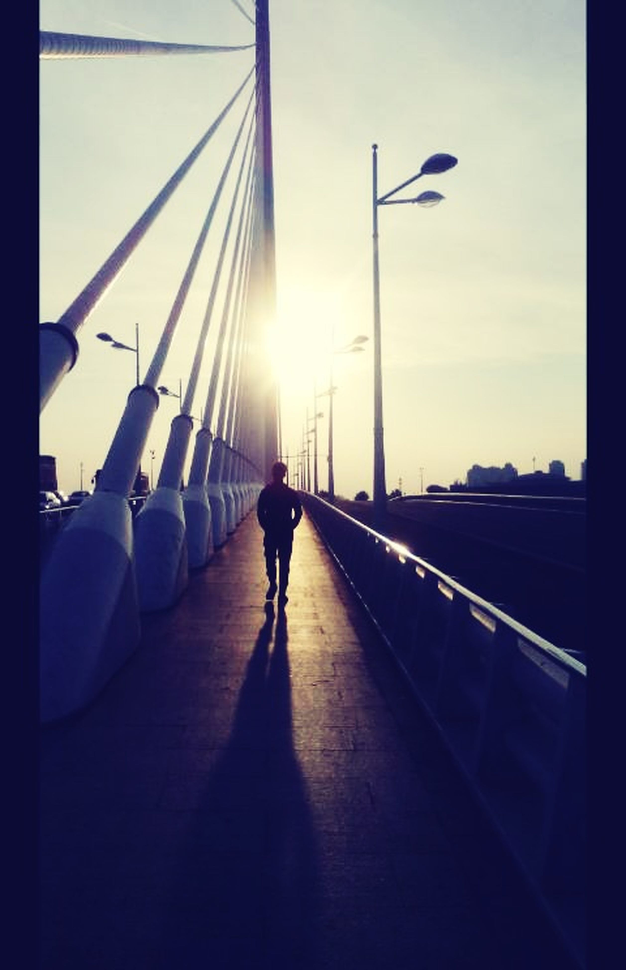 transportation, sunlight, walking, the way forward, men, lifestyles, sun, built structure, architecture, sky, silhouette, rear view, sunbeam, full length, leisure activity, sunset, diminishing perspective, person