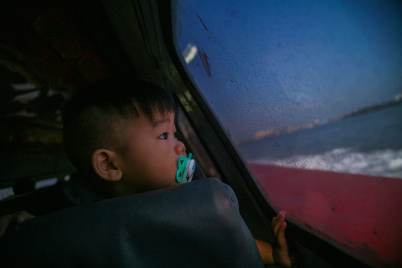 A child looks out of a ferry window enroute from Pulau Ketam to Klang jetty on February 26, 2016 in Pulau Ketam, Malaysia. Pulau Ketam literally means 'Crab Island' and almost 80% of the population are fishermen. Around 6,000 people live permanently on the island, the majority of which are Chinese. Photo by Samsul Said Boat Children, Day Headshot Malaysia, Beach, Blue, Boat, Bright, Coast, Colorful, Despair, Editorial, Fisherman, Fishing, Flag, Ghana, Heat, Holiday, Landscape, Nature, Net, Ocean, Poor, Poverty, Rural, Sand, Sea, Seafood, Tourism, Traditional, Travel, Tropical, Vacation, Village, W Photojournalism Portrait Sky, The Photojournalist - 2015 EyeEm Awards The Photojournalist - 2016 EyeEm Awards