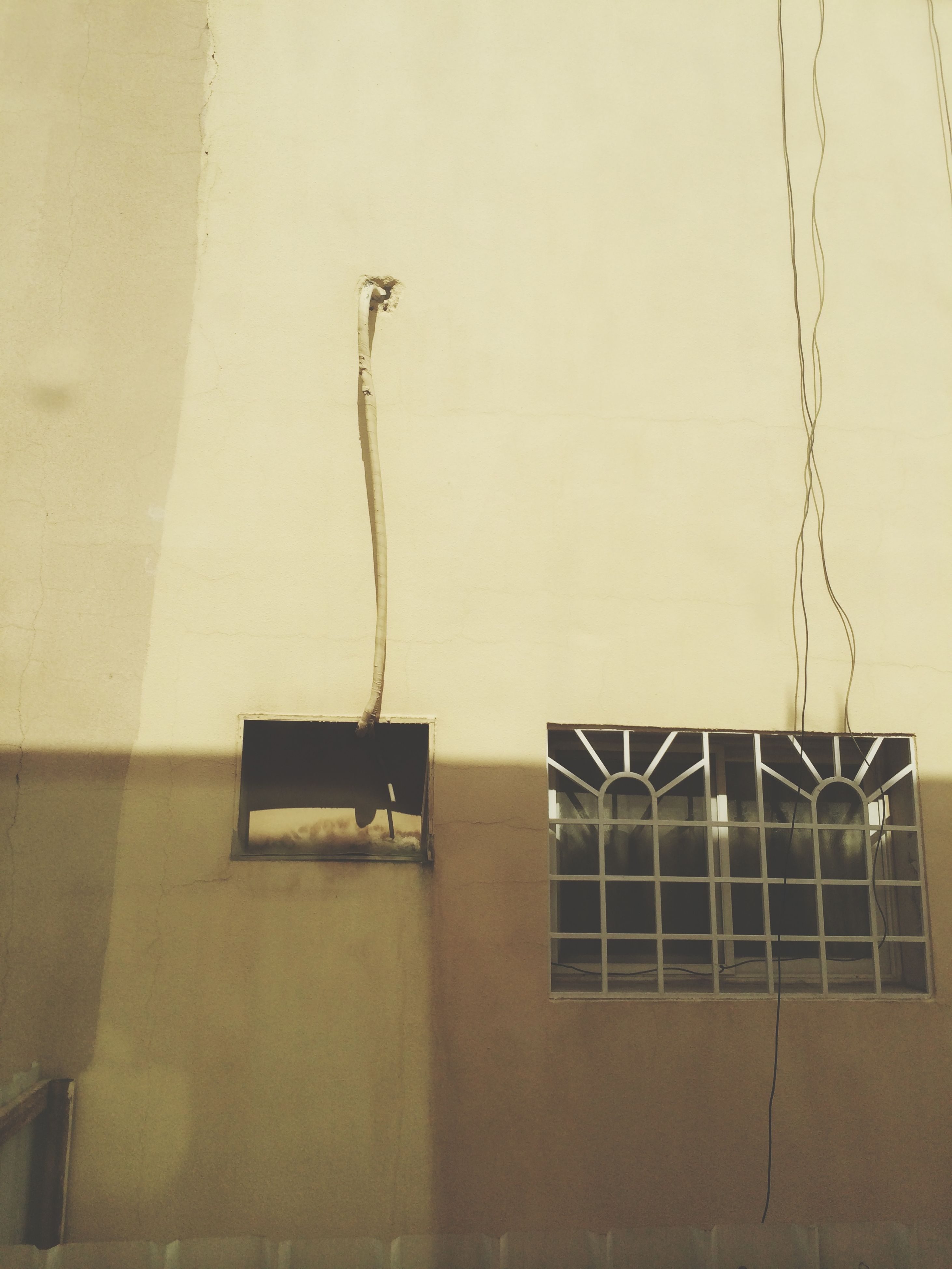 wall - building feature, built structure, architecture, electricity, building exterior, wall, low angle view, hanging, no people, house, indoors, cable, power line, shadow, day, window, lighting equipment, power supply, sunlight