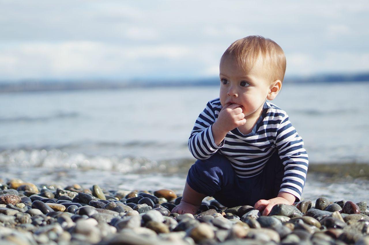 Baby Sitting On Pebbles At Seashore