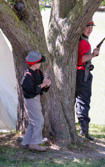 June 26, Hesston Indiana USA ; two brothers hide as they play a shoot out game during a civil war days event at the Hesston steam museum Hiding In Plain Sight Old Fashioned Toys Boys Casual Clothing Childhood Costumes Day Full Length Guns Happiness Holding Leisure Activity Lifestyles Nature Outdoors People Playing Reenactment Side View Smiling Standing Togetherness Tree Trunk Two People