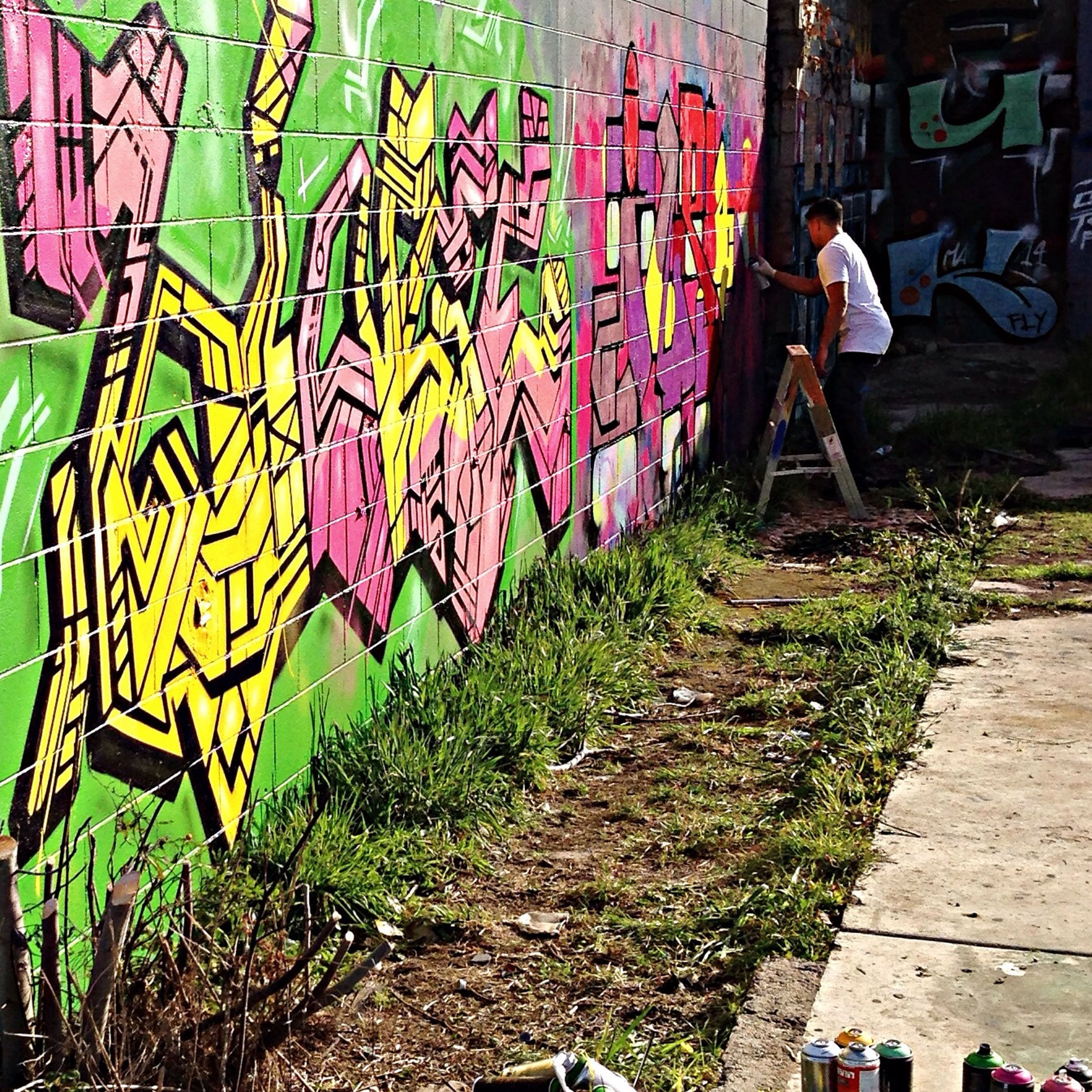 graffiti, multi colored, art, lifestyles, creativity, wall - building feature, art and craft, men, built structure, leisure activity, street, street art, day, outdoors, architecture, casual clothing, standing, full length