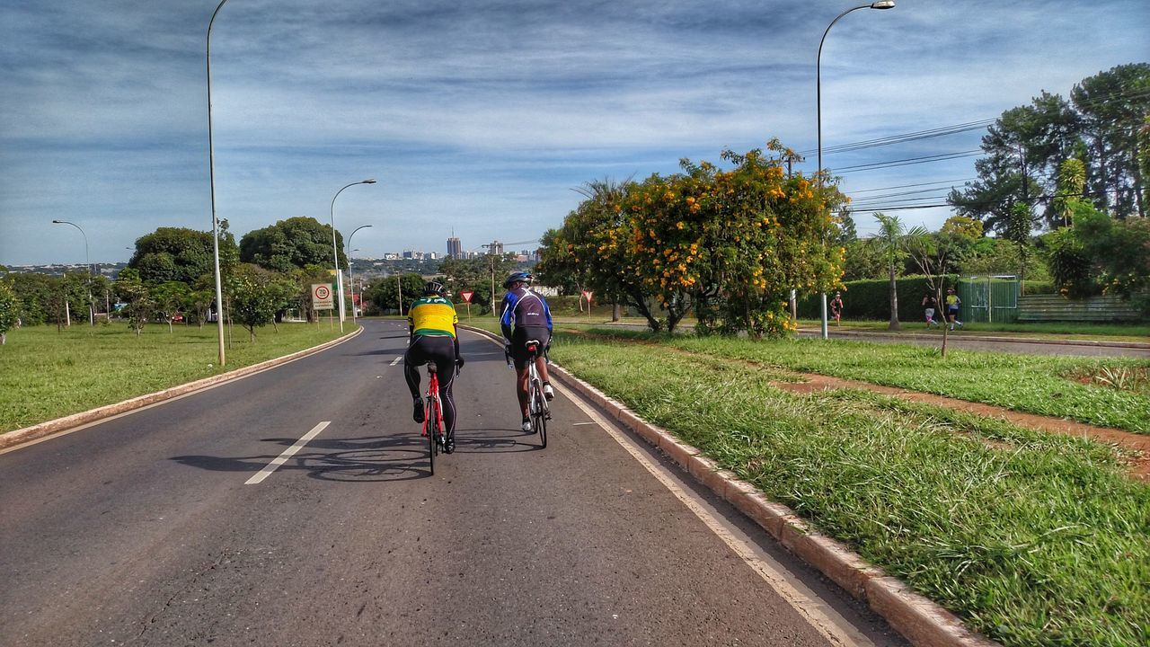 tree, real people, transportation, men, day, sky, outdoors, road, lifestyles, bicycle, full length, land vehicle, cloud - sky, nature, two people, women, grass, architecture, people
