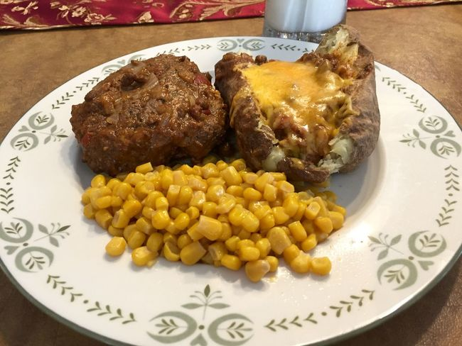 Hamburger Steak and baked potato covered with chili. Baked Potato Cheese Chili  Close-up Corn Food Freshness Hamburger Hamburger Steak Indulgence Meal Milk No People Plate Potato Ready-to-eat Served Serving Size Still Life Sweetcorn