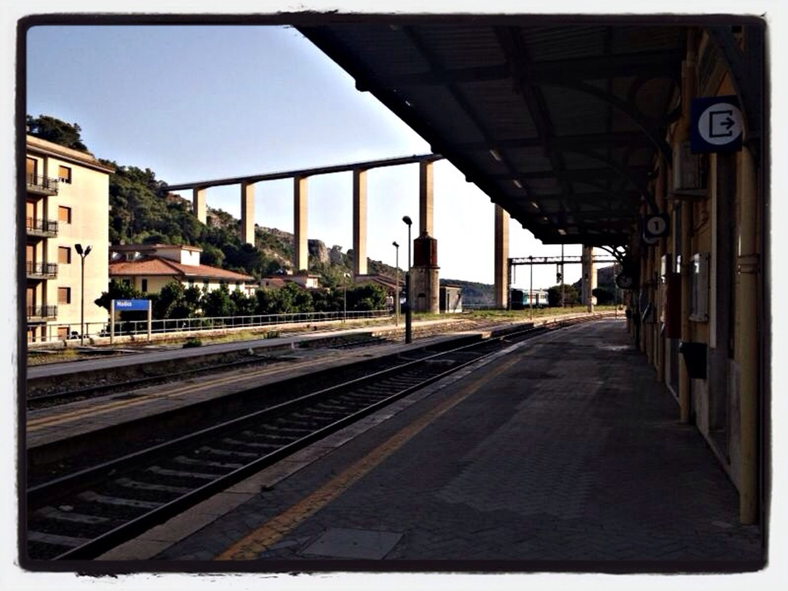 railroad track, transportation, rail transportation, architecture, built structure, transfer print, public transportation, railroad station platform, railroad station, the way forward, diminishing perspective, building exterior, auto post production filter, clear sky, vanishing point, sky, train - vehicle, railway track, empty, long