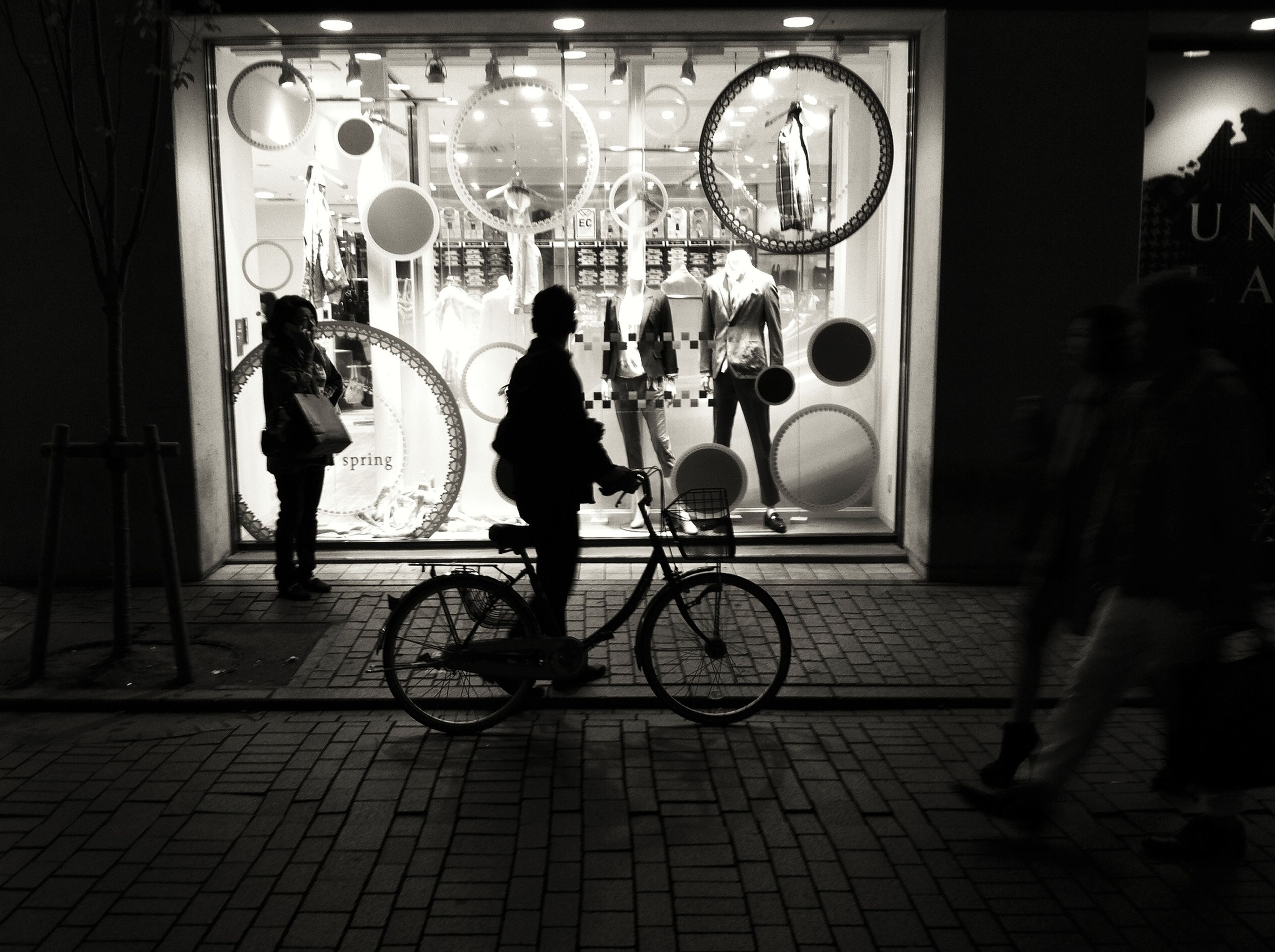 men, bicycle, lifestyles, full length, leisure activity, walking, person, street, indoors, built structure, city life, transportation, architecture, city, illuminated, medium group of people, rear view, night