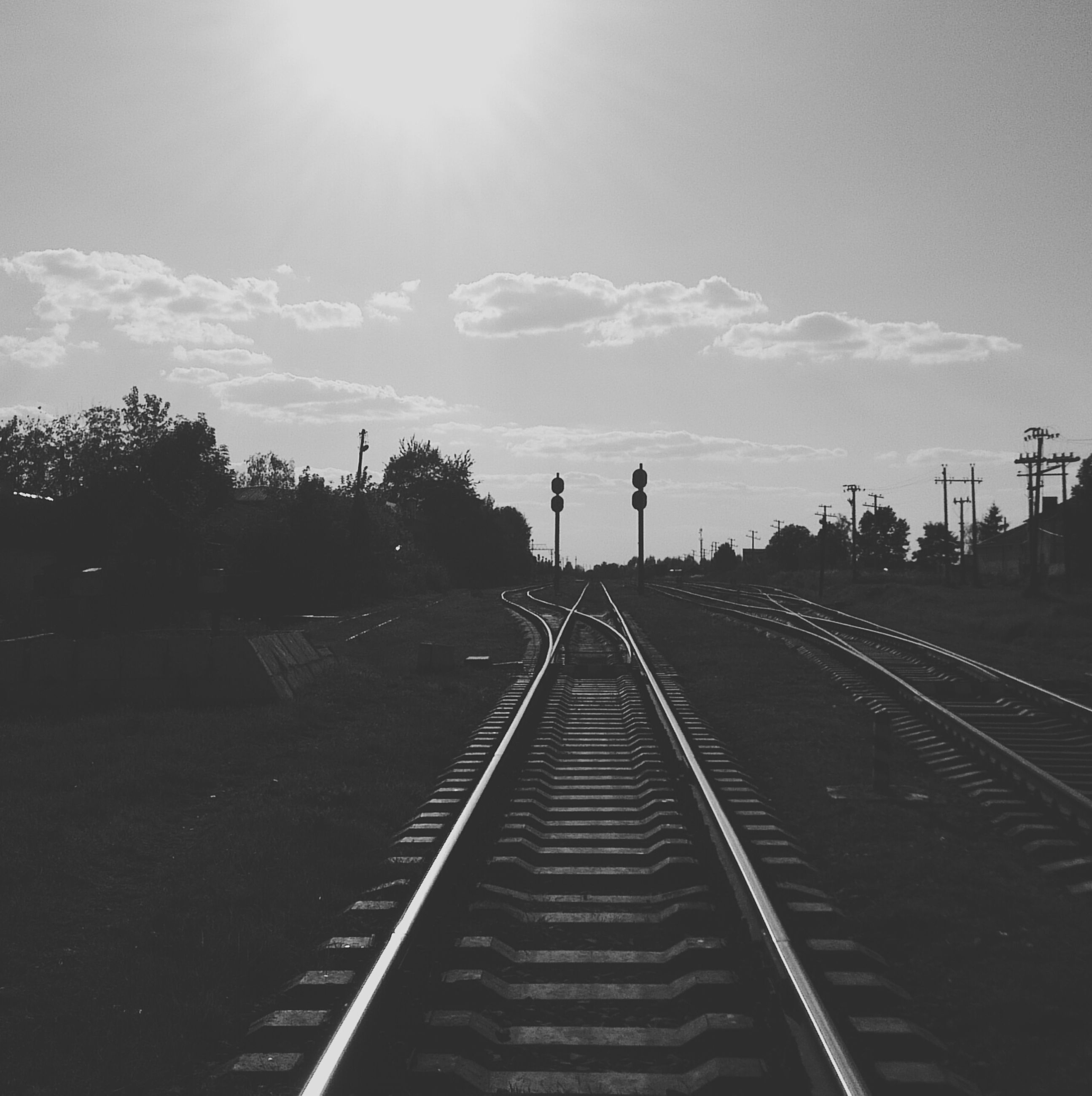 the way forward, railroad track, sky, vanishing point, diminishing perspective, transportation, sun, sunlight, rail transportation, sunbeam, cloud - sky, lens flare, cloud, tree, outdoors, nature, day, sunset, tranquility, long