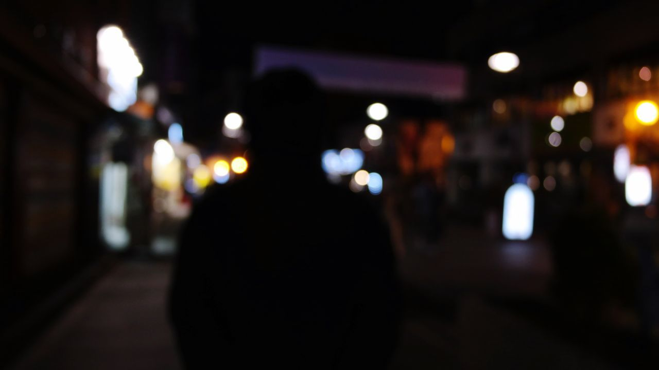 illuminated, night, incidental people, focus on foreground, real people, built structure, rear view, walking, silhouette, indoors, defocused, architecture, one person, men, women, building exterior, city, close-up, people