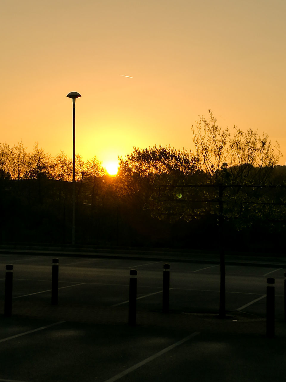 sunset, street light, tree, silhouette, no people, sun, outdoors, tranquility, tranquil scene, sky, nature, scenics, beauty in nature, illuminated