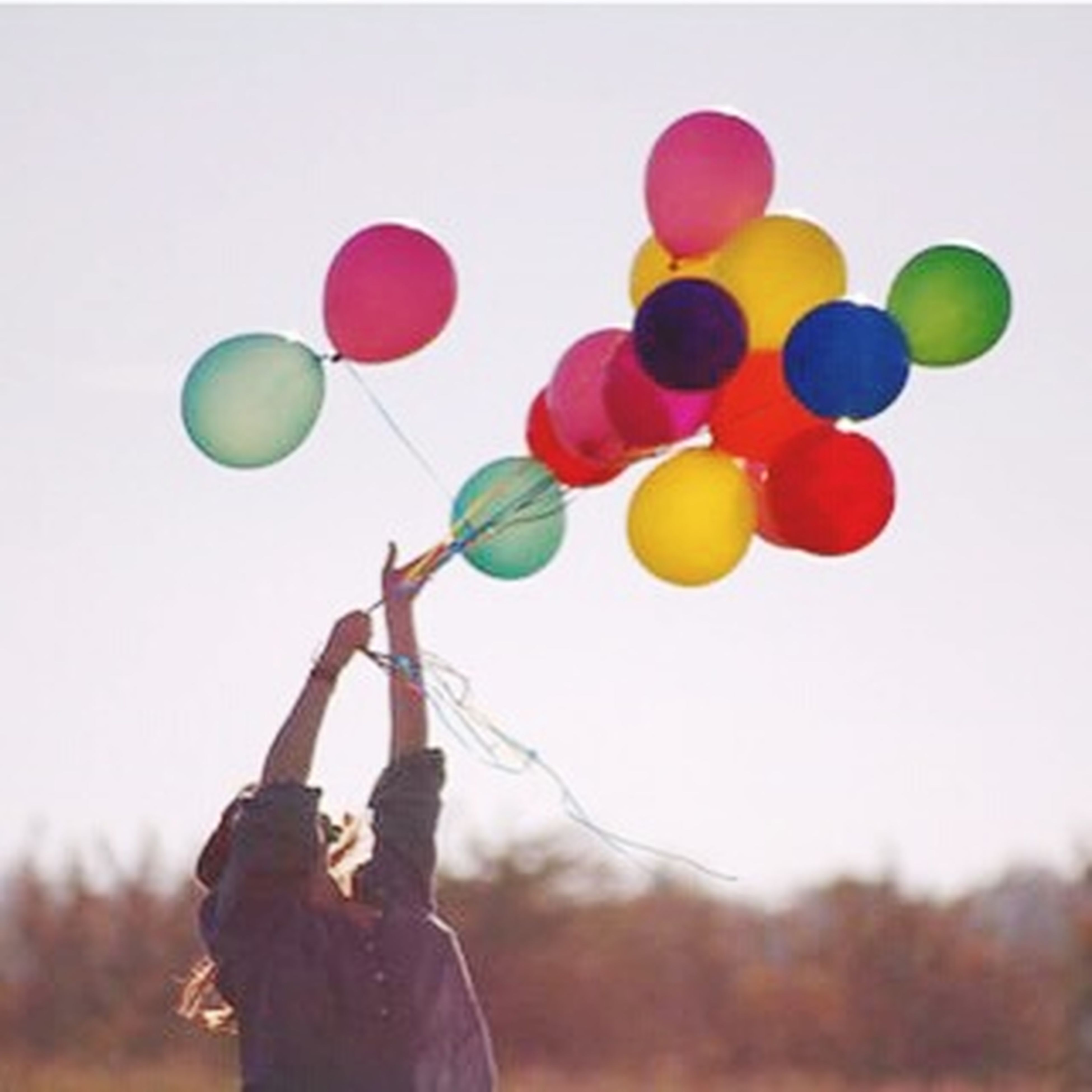 multi colored, balloon, leisure activity, mid-air, clear sky, sky, colorful, copy space, holding, lifestyles, unrecognizable person, childhood, low angle view, variation, hot air balloon, sport, person, toy