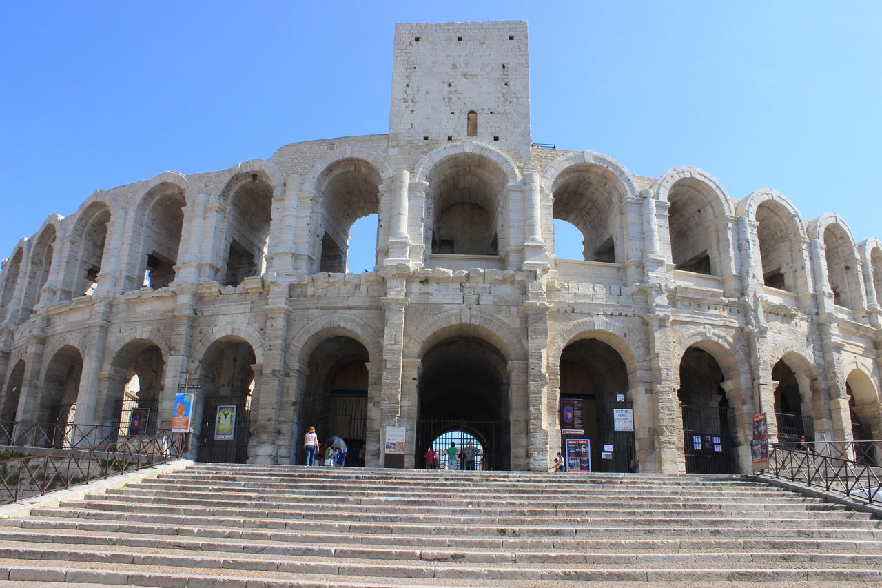 Adult Amphitheater Ancient Ancient Civilization Arch Architecture Arles Blue Built Structure Day History Large Group Of People Old Ruin Outdoors People Sky Sunlight The Past Tourism Tourist Travel Travel Destinations